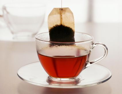 Teabag being lifted from glass cup of tea