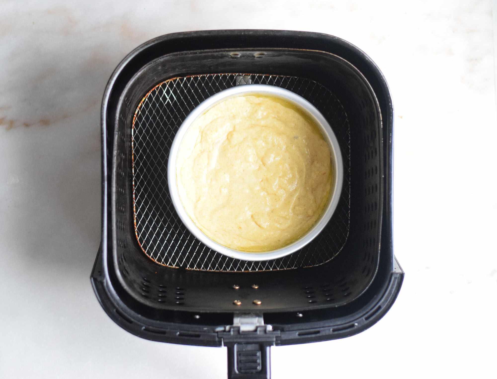 cornbread batter in a pan in an air fryer basket