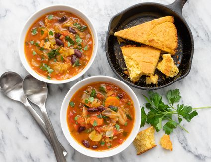 instant pot vegetable soup in bowls with cornbread wedges