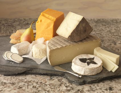 yellow and white cheeses sitting on a slate board