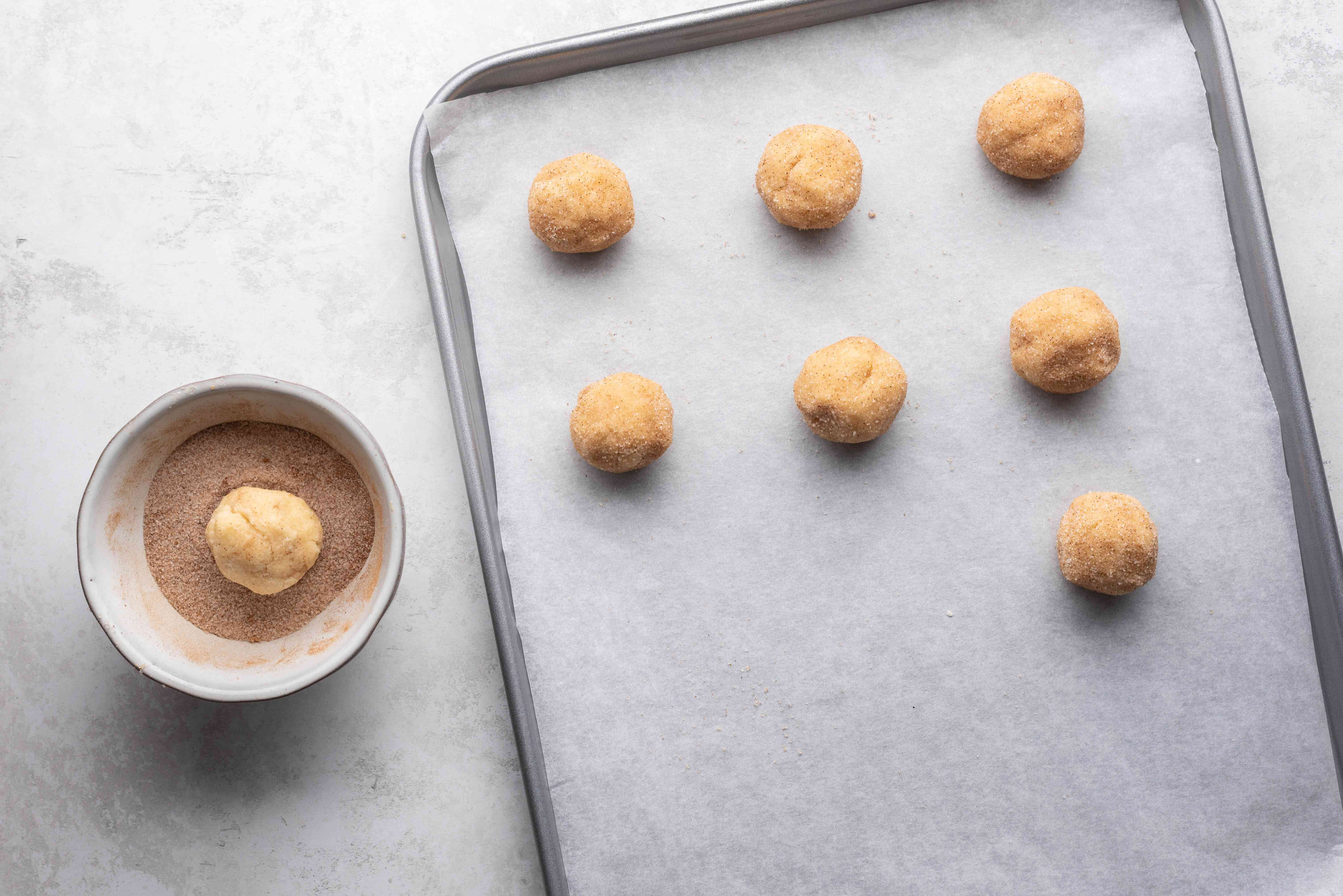 cookie dough balls on a parchment paper lined baking sheet