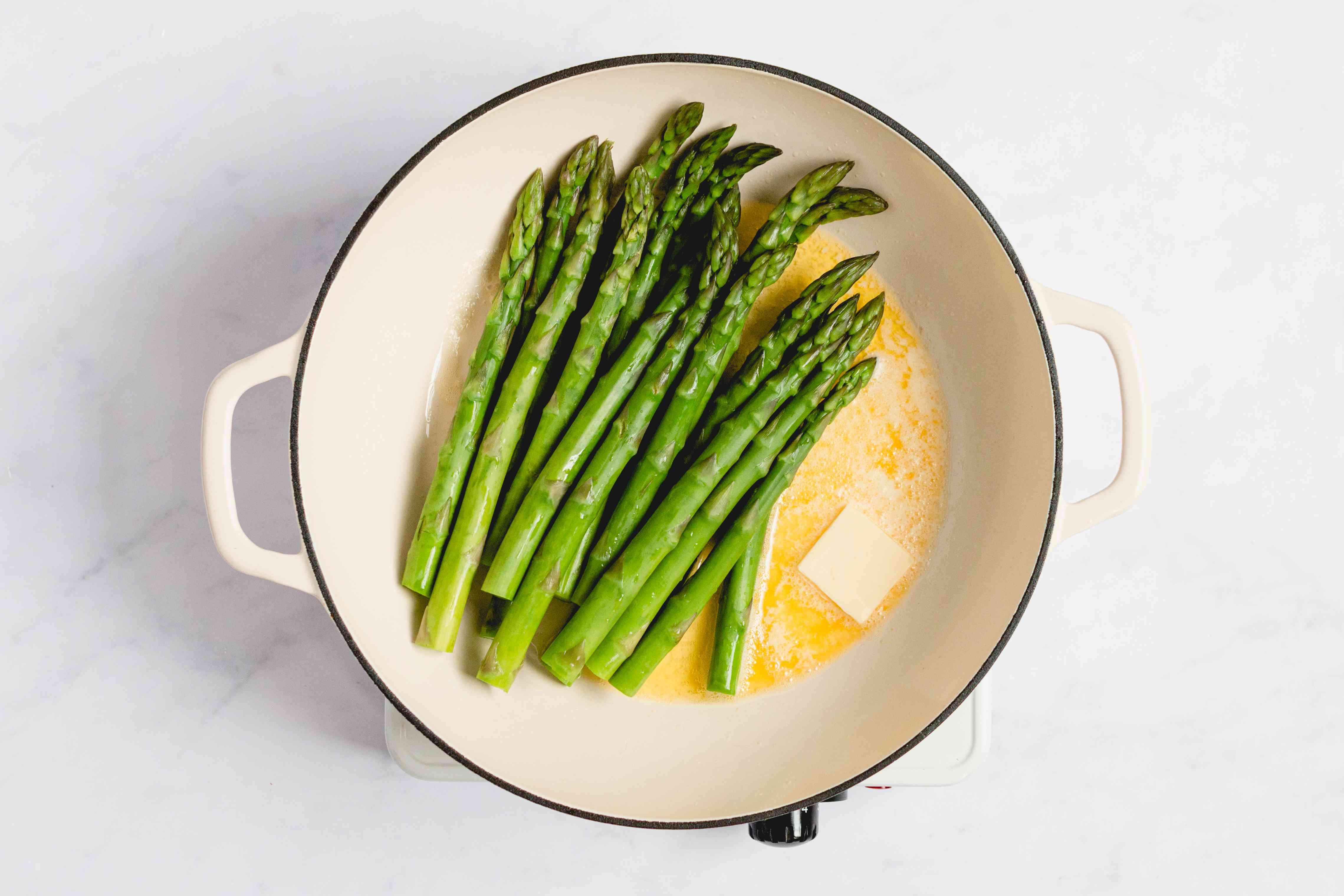 Asparagus cooking in a saucepan with butter