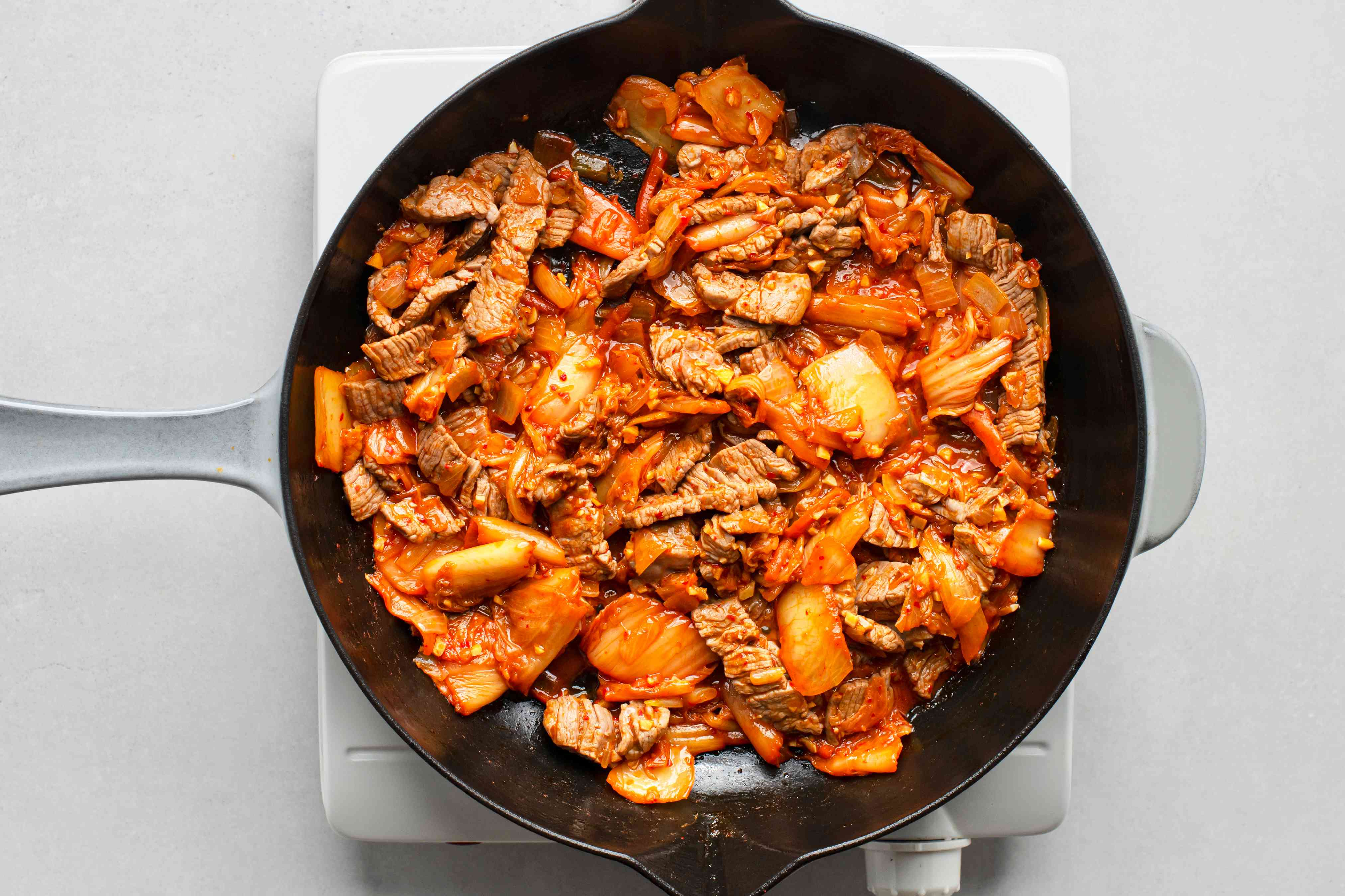 Add the meat to the kimchi mixture and continue to sauté
