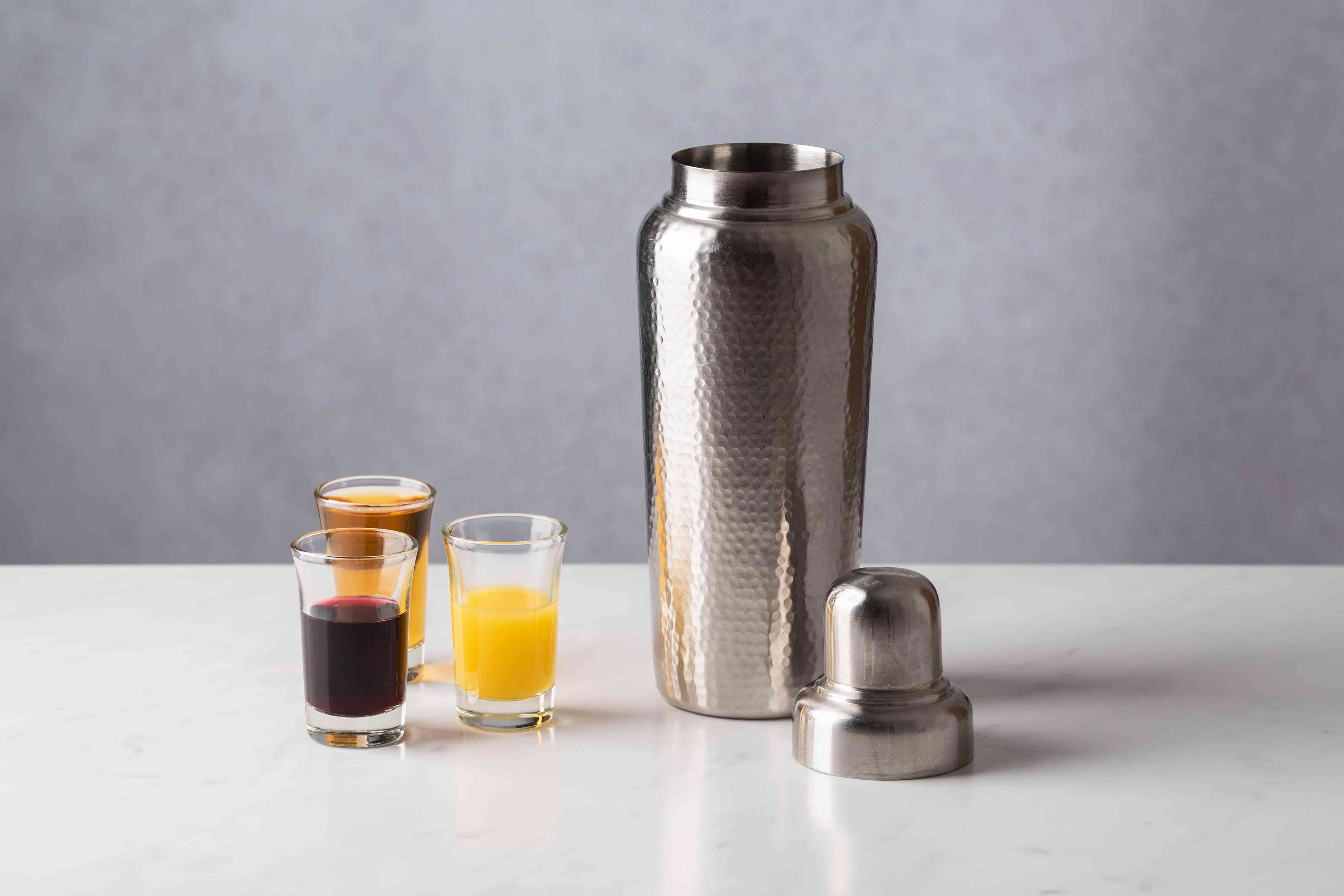 brandy, port, and orange juice in shot glasses, cocktail shaker filled with ice