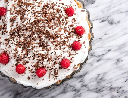Easy chocolate pie sprinkled with chocolate shavings and dotted with fresh raspberries