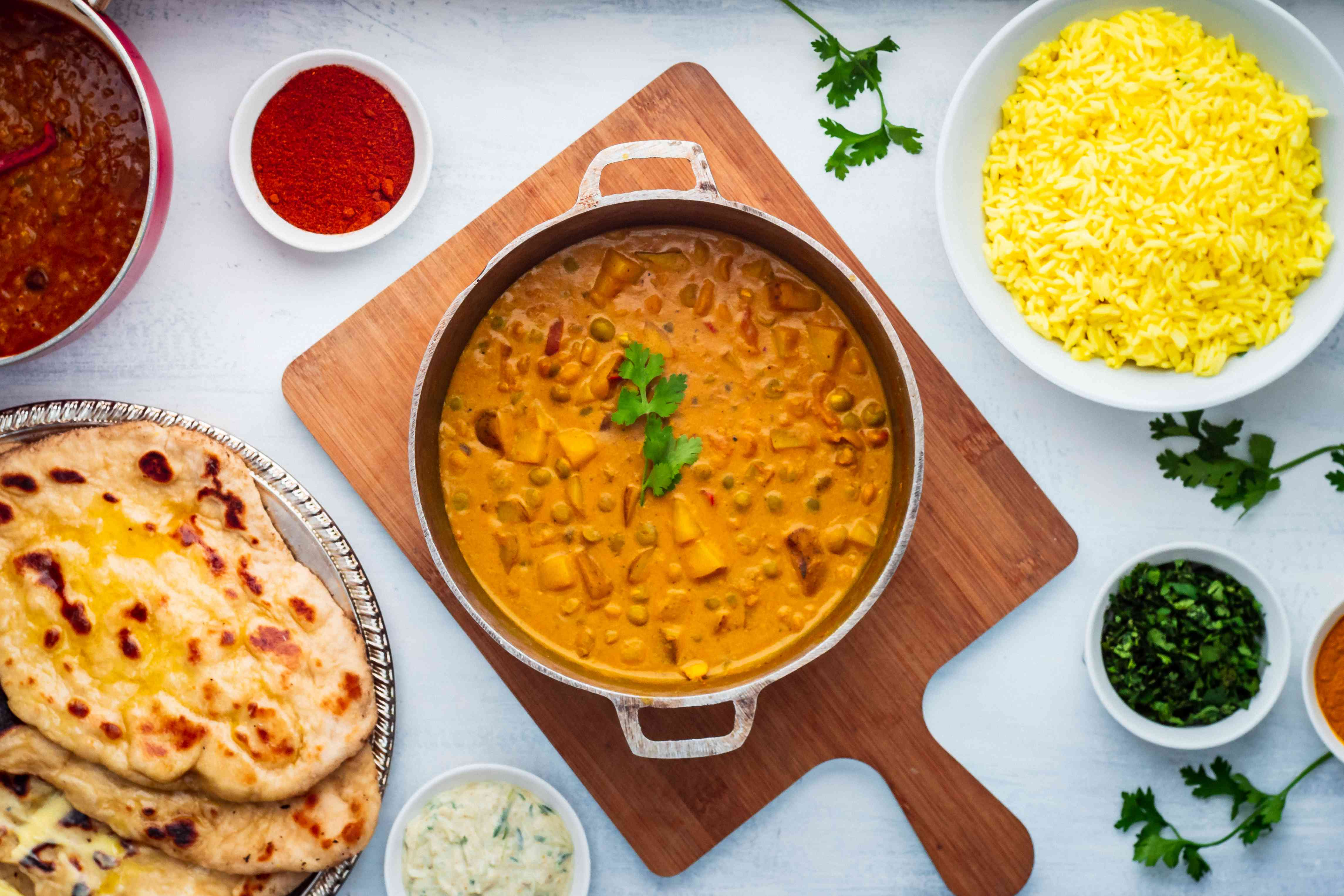 Curry with pea and potato with rice bowl, dal, naan bread, and spices.