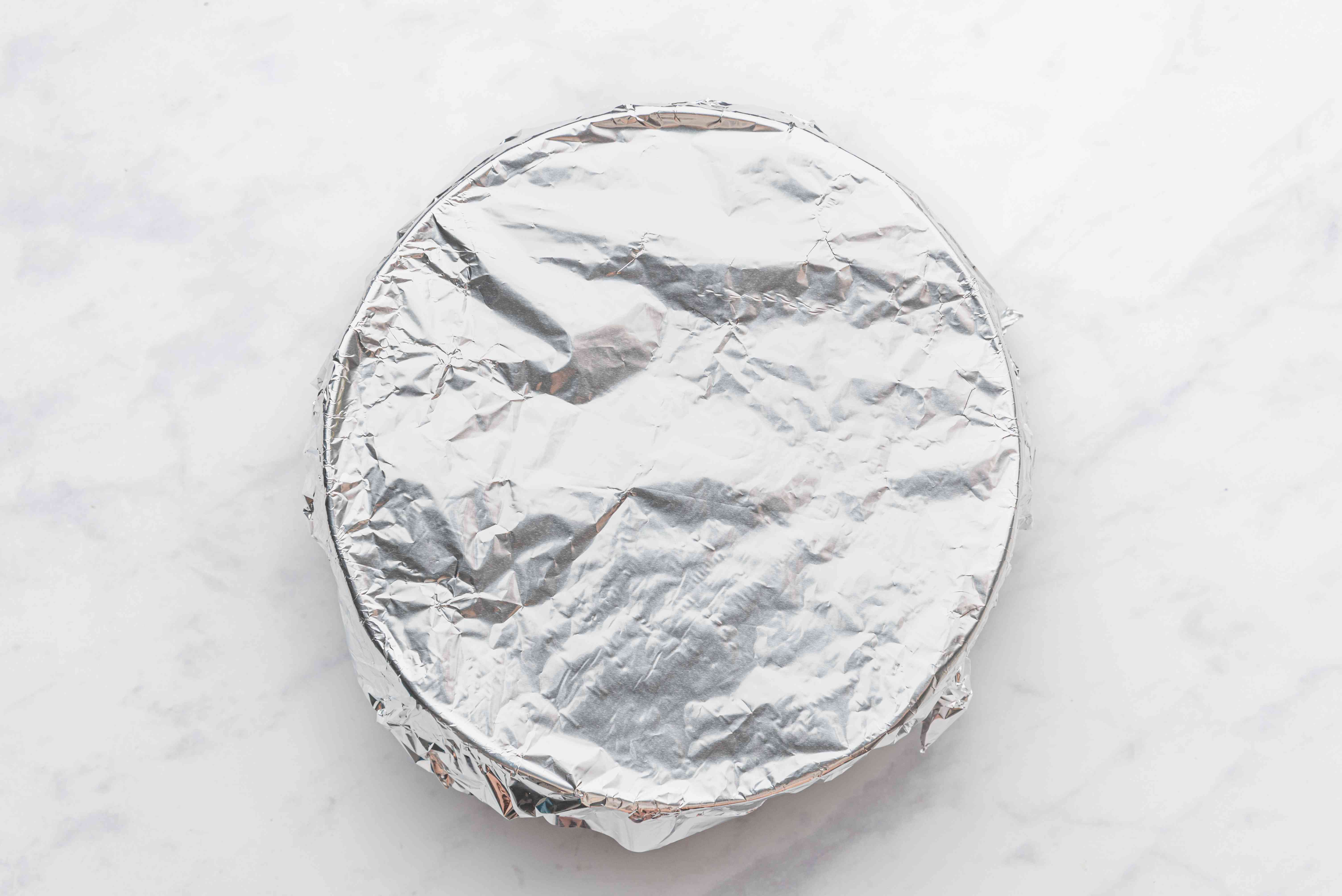 Salted vegetables thoroughly combined in a bowl, covered with aluminum foil