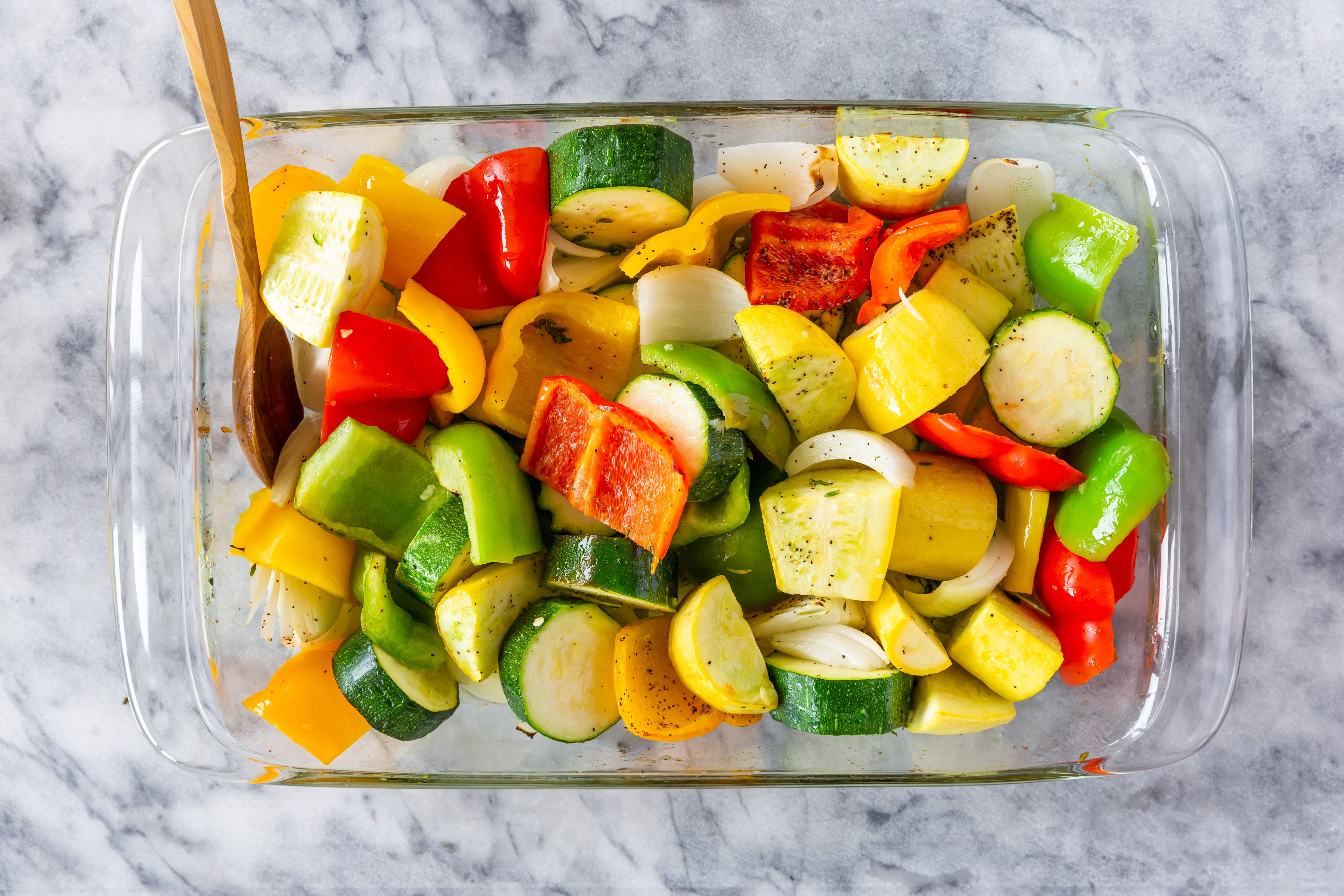 Wooden spoon tossing vegetables in baking dish