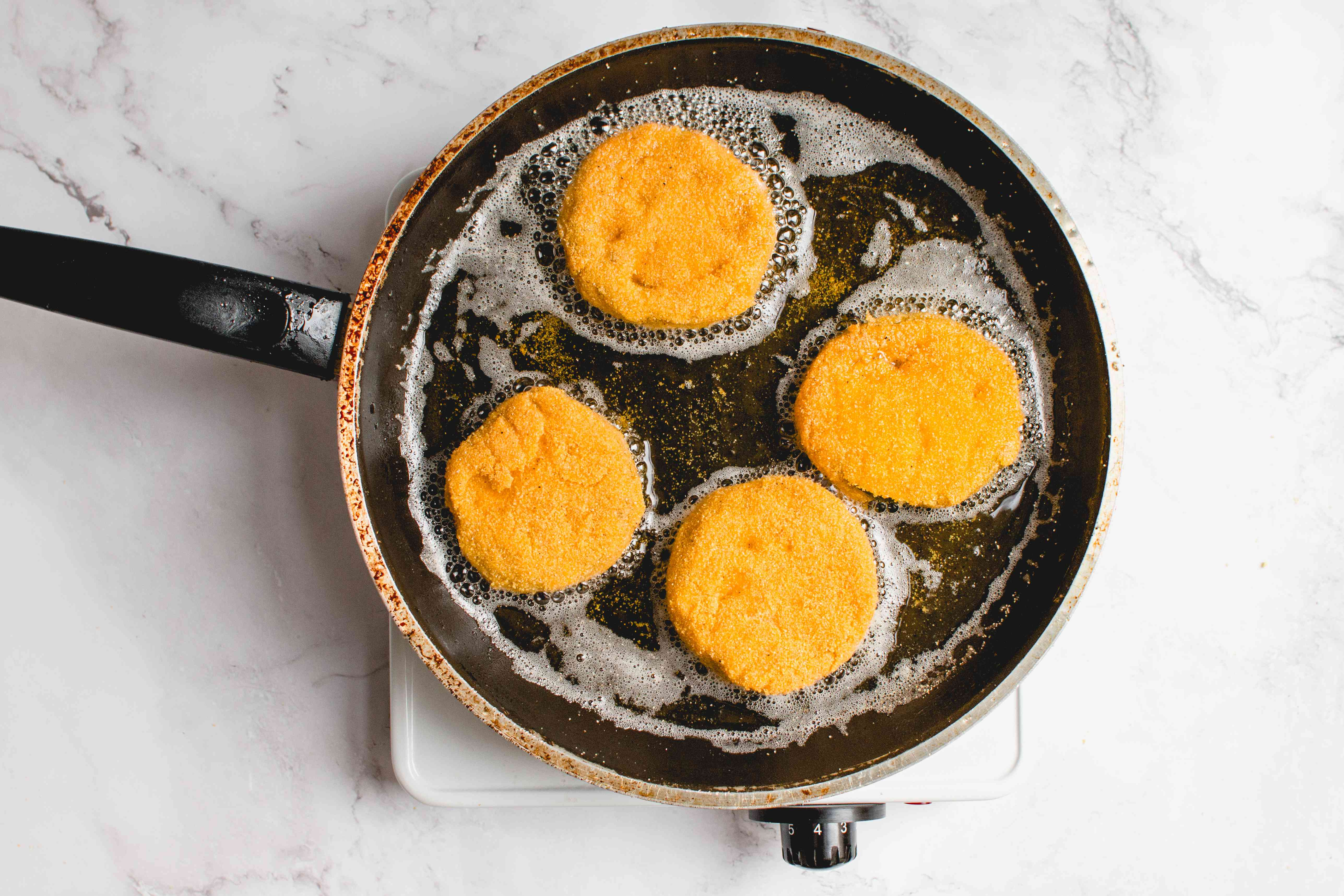 frying cornmeal coated tomatoes in the skillet