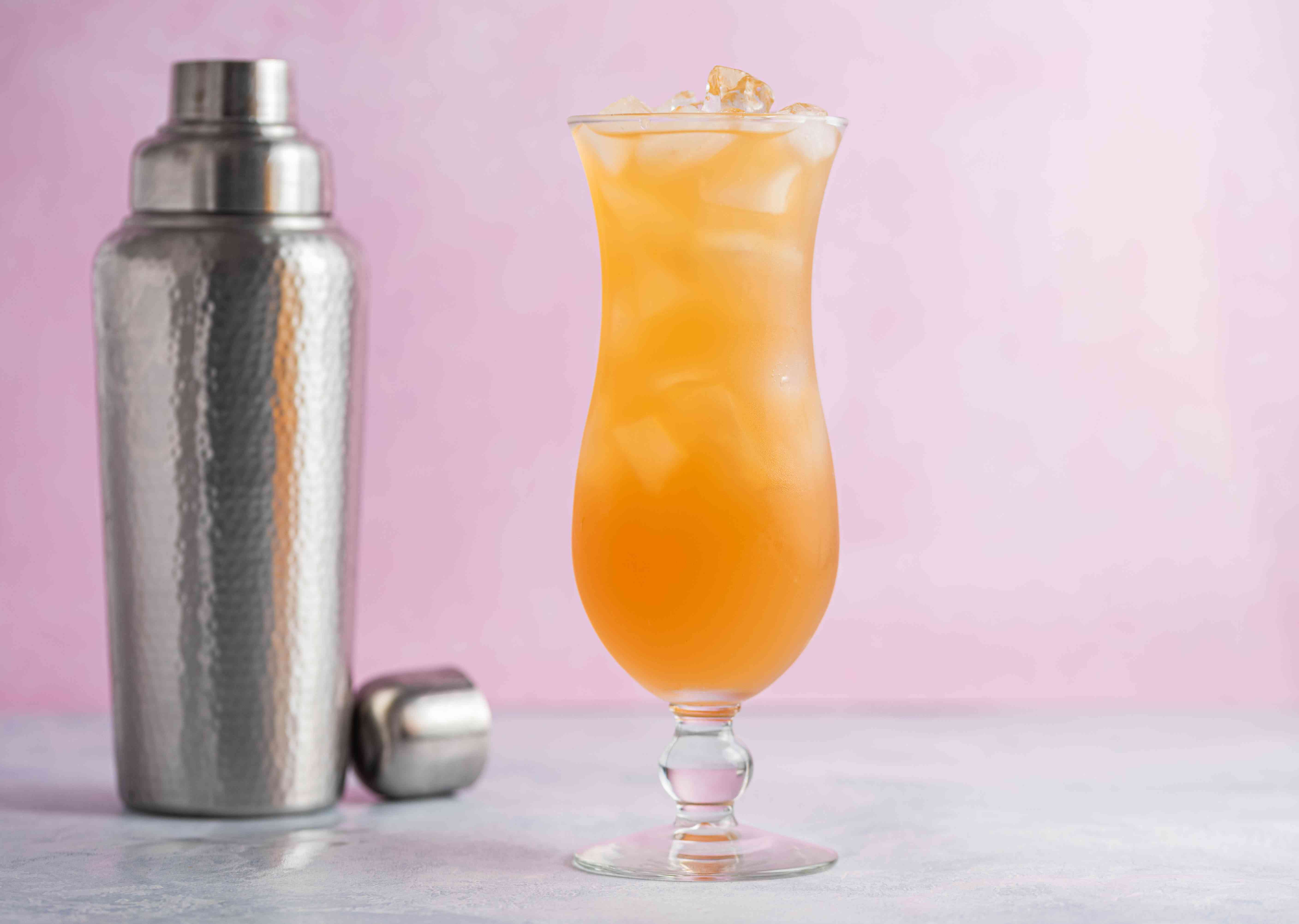 A hurricane cocktail and a hammered metal cocktail shaker