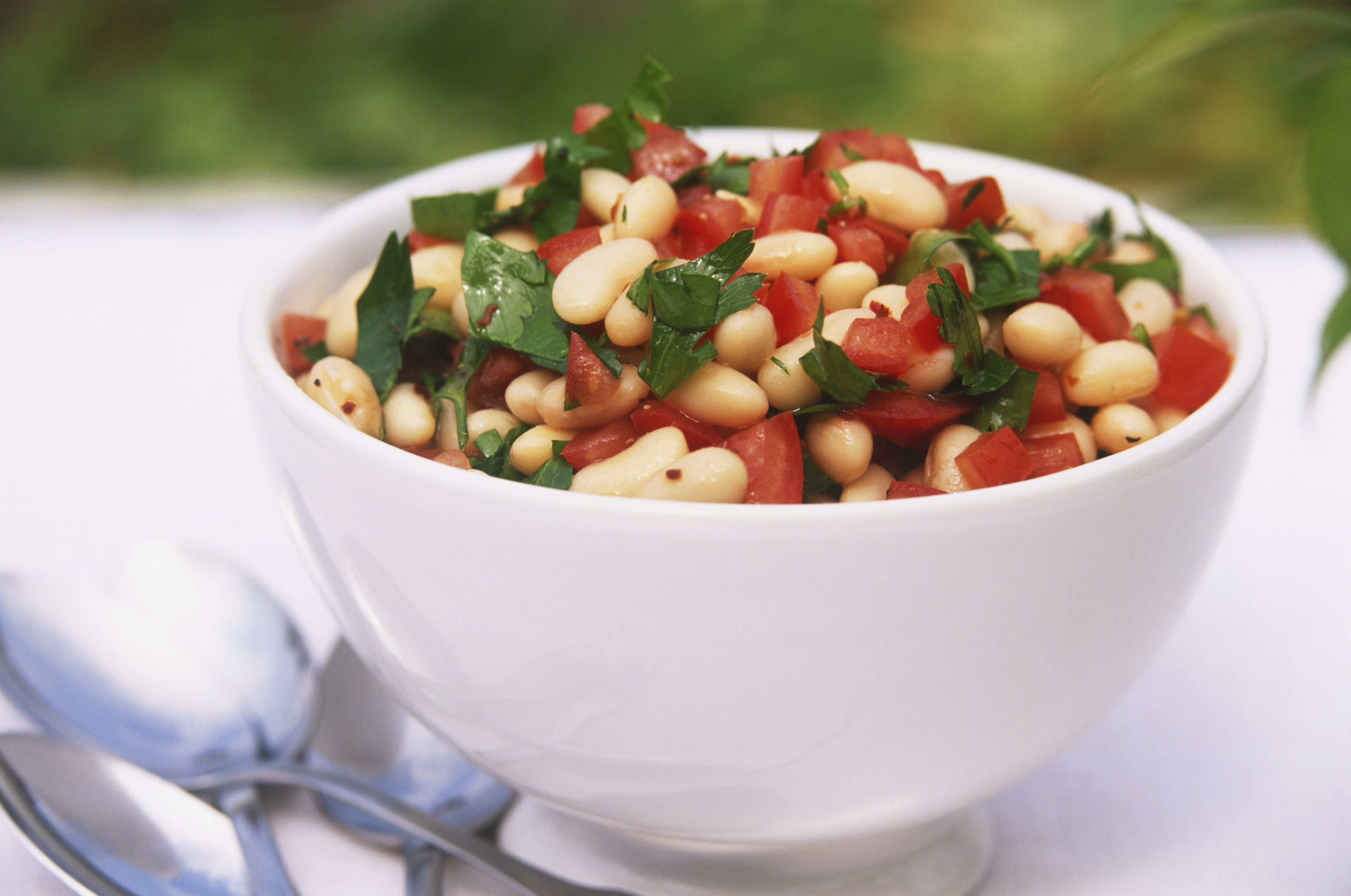 White bowl containing marinated beans and tomato salad, garnished with coarsely chopped parsley