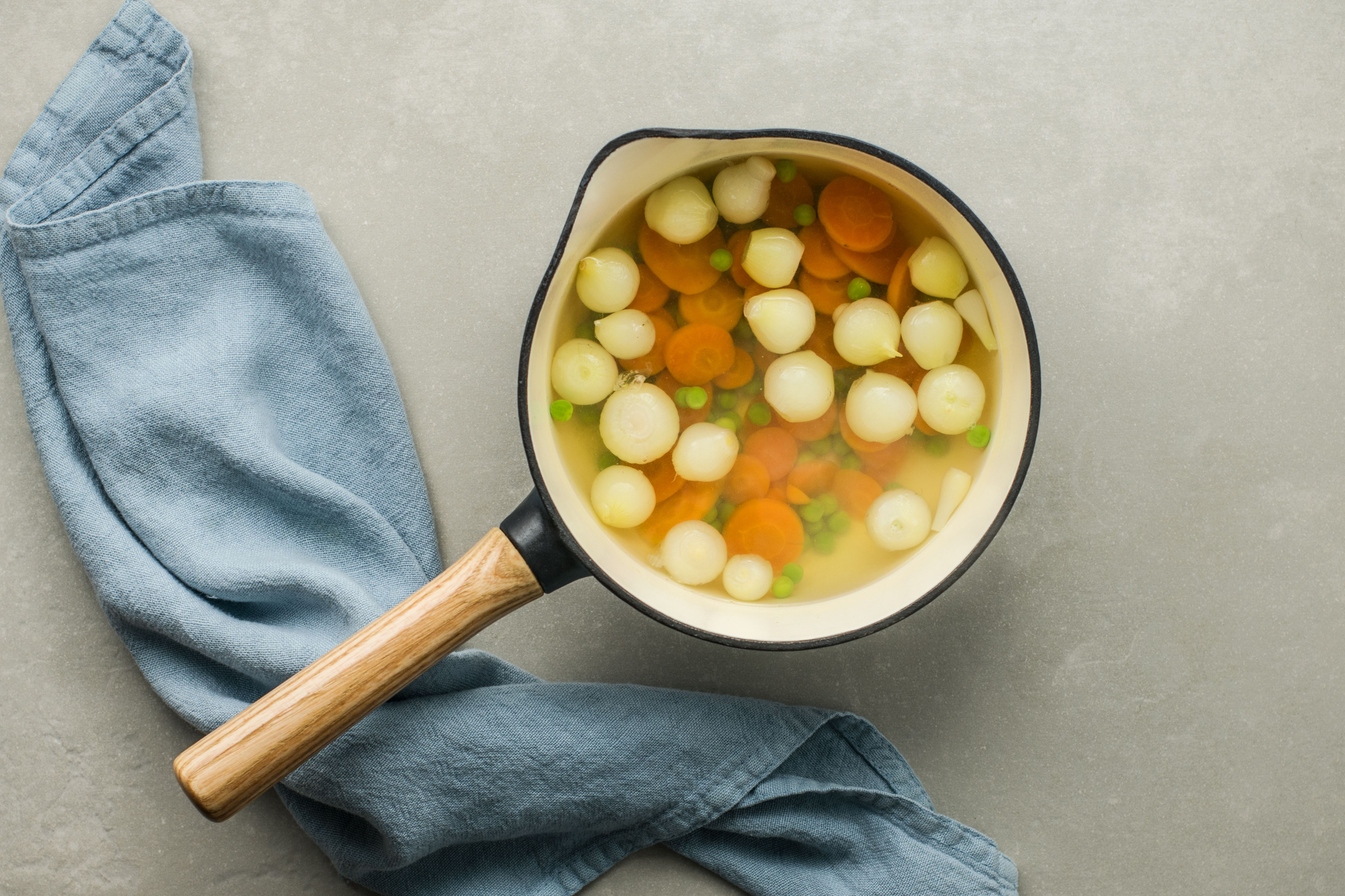 Cooked onions, peas, and carrots in a saucepan
