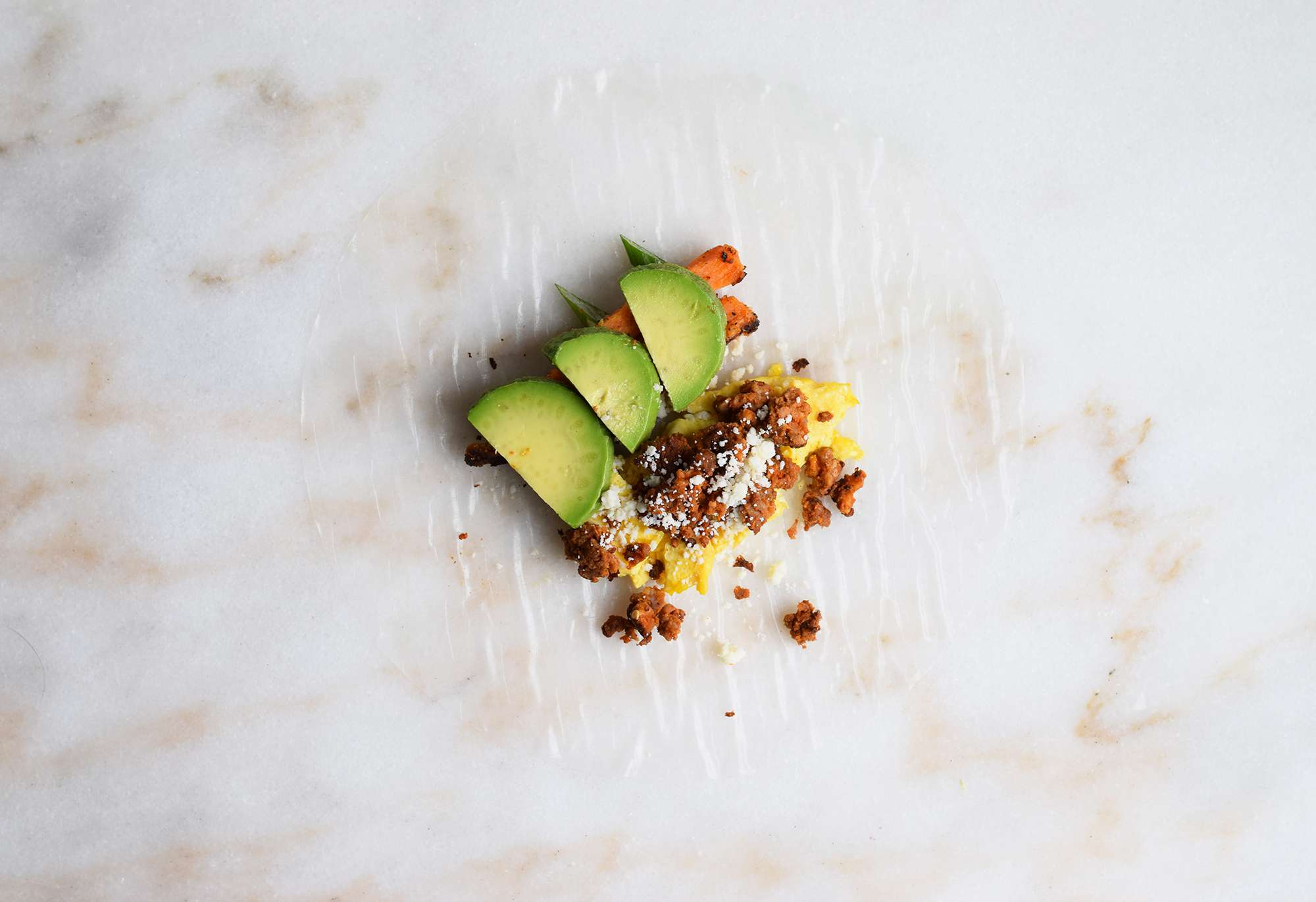rice paper wrapper topped with eggs, chorizo, avocado, and sweet potato
