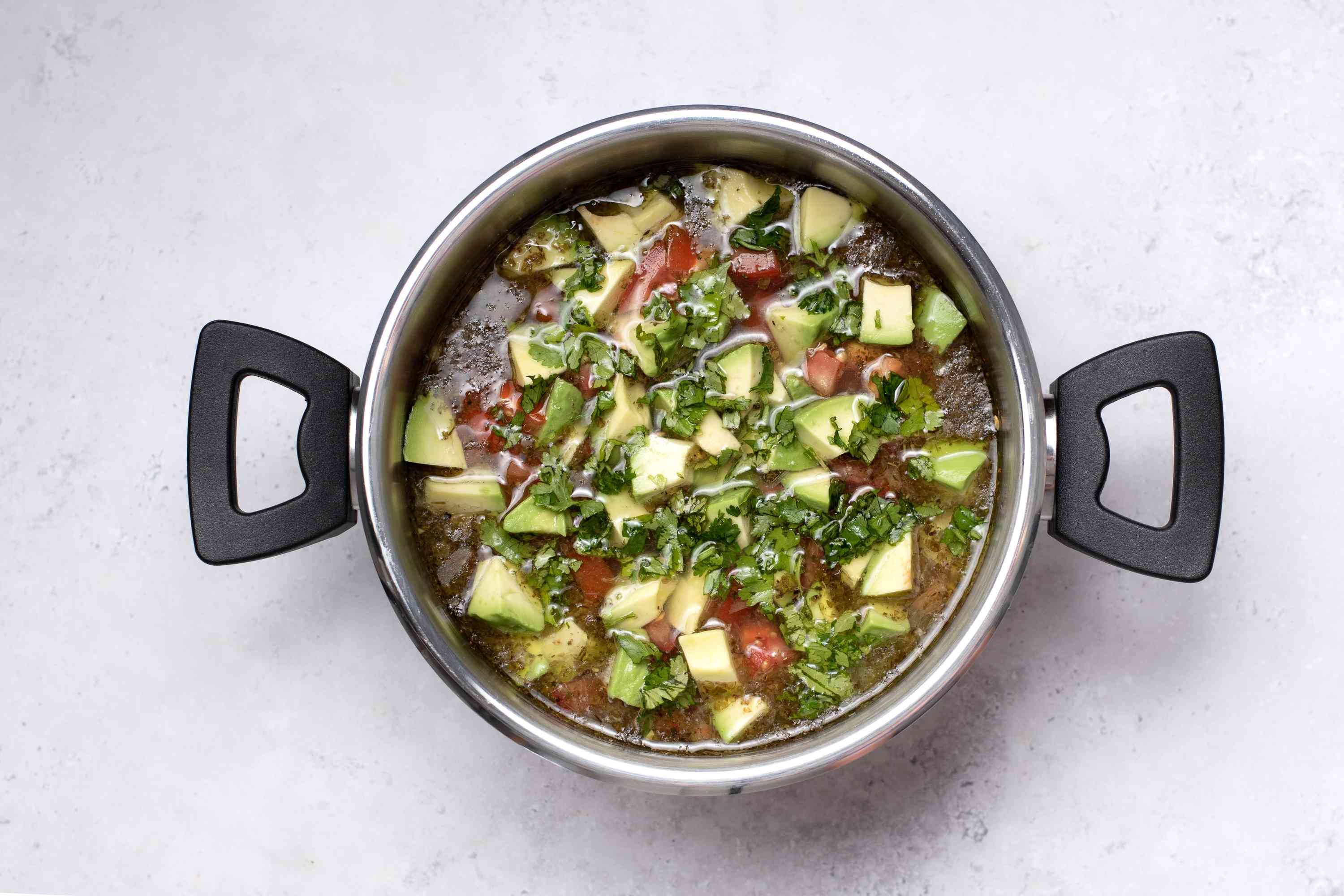 Chicken Avocado Soup (With Variations), cilantro and avocado added to the soup in the pot