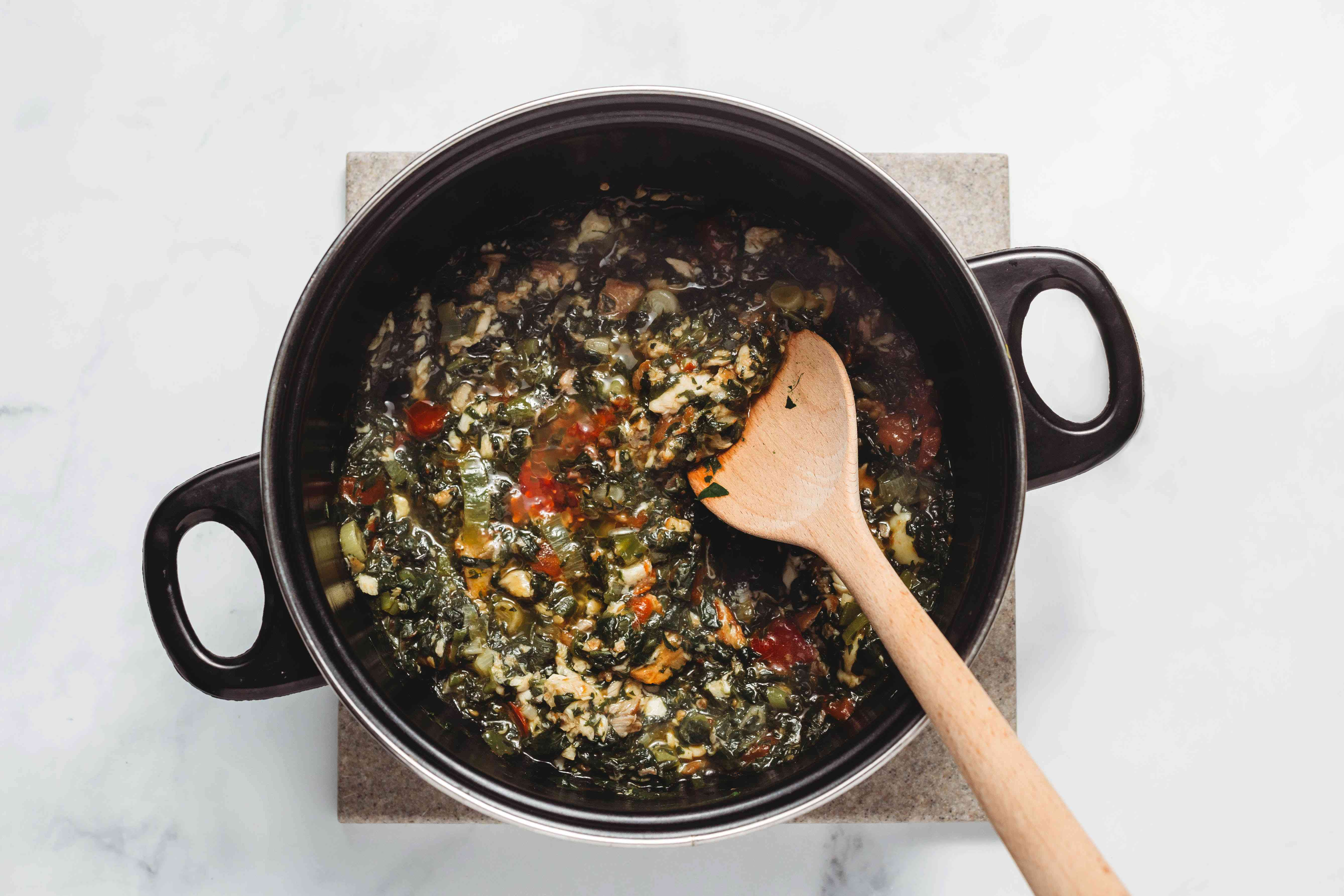 mixing spinach, tomato and onion mixture in a large pot with a wooden spoon