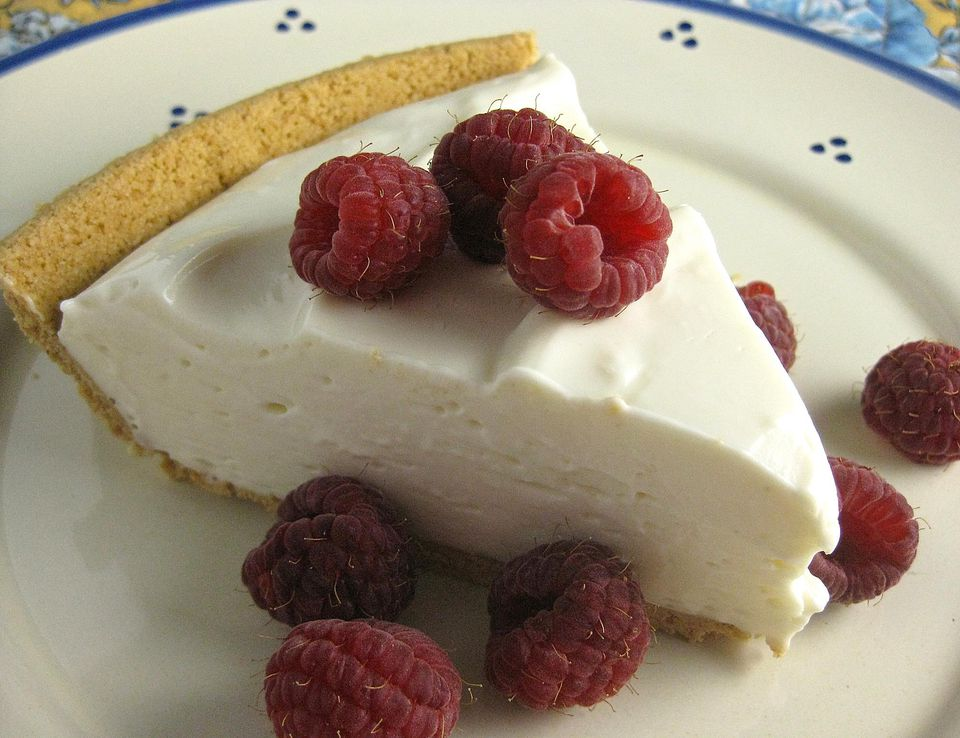 Close up of cheese cake and raspberries on plate.