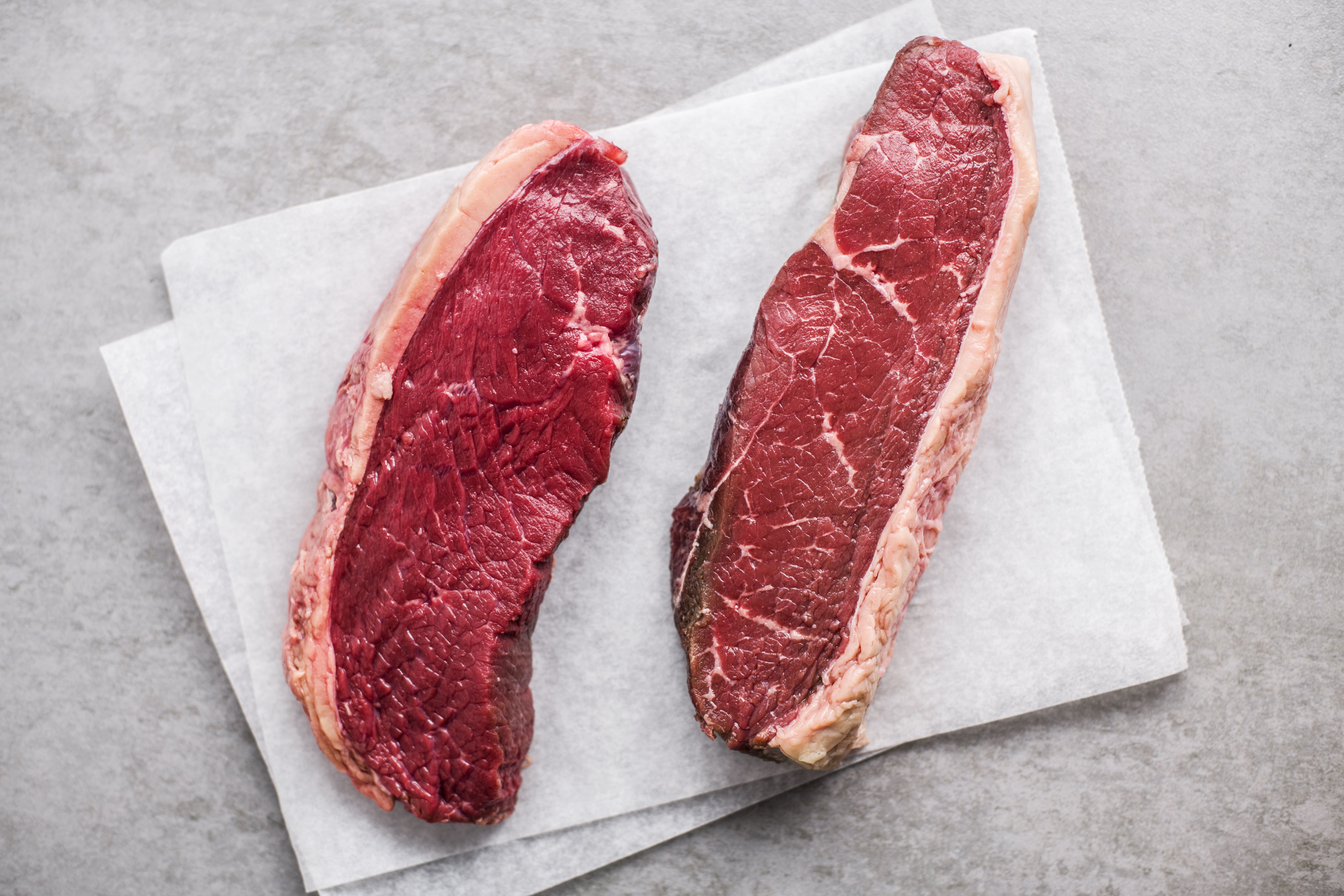 Steaks sitting out on the countertop