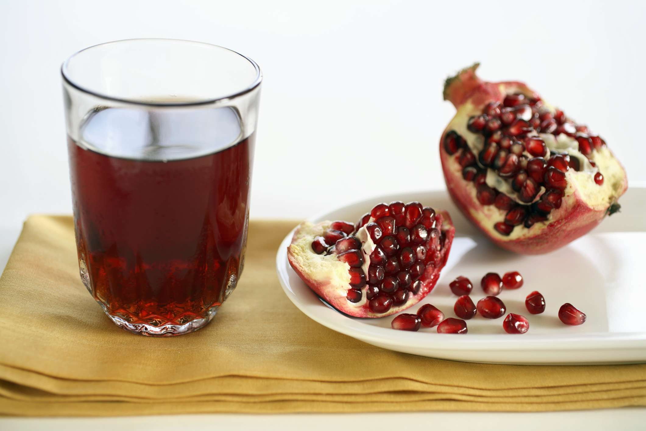 A glass of pomegranate juice next to pomegranate seeds