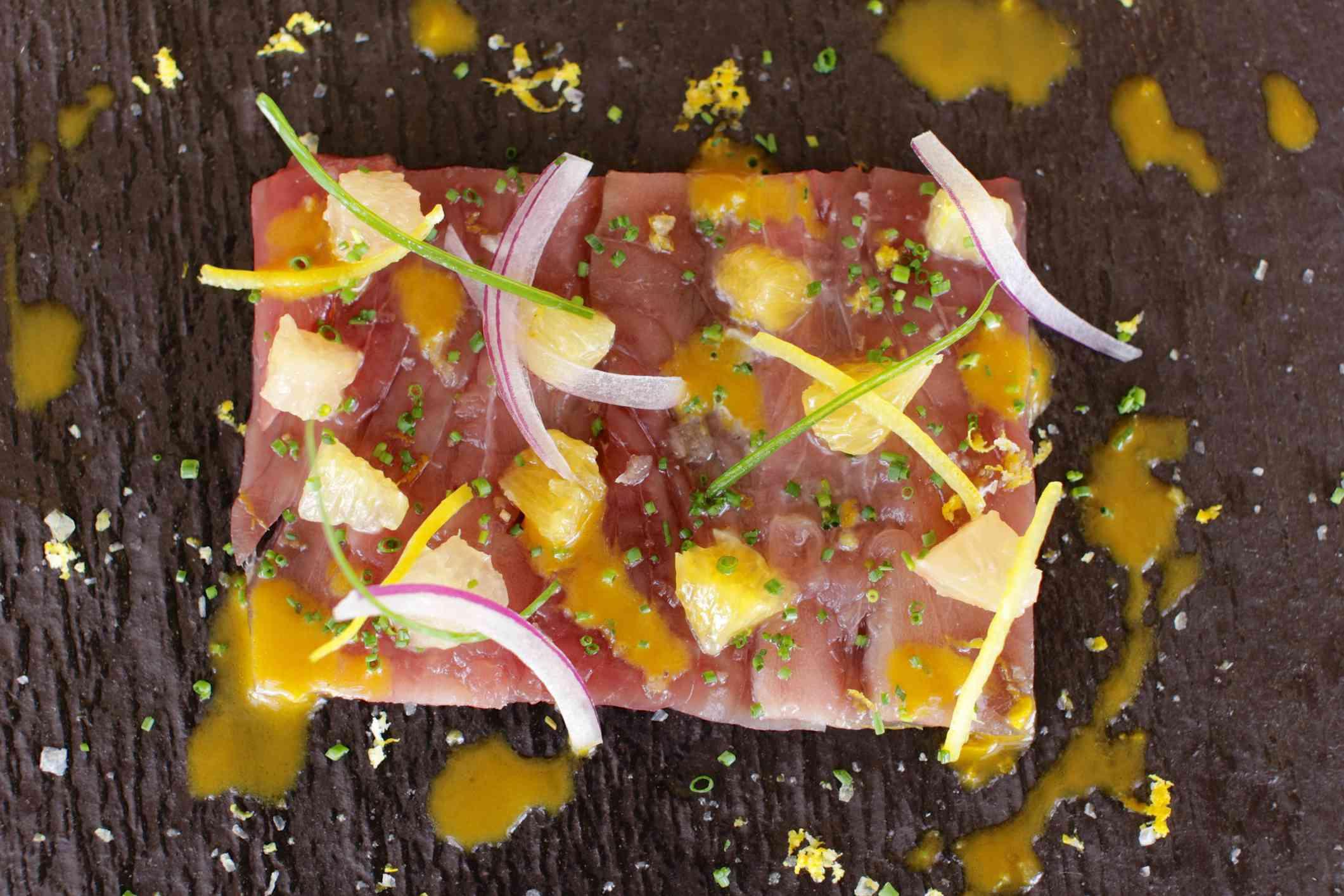Tuna tiradito, red onion, citrus segments and ají amarillo sauce