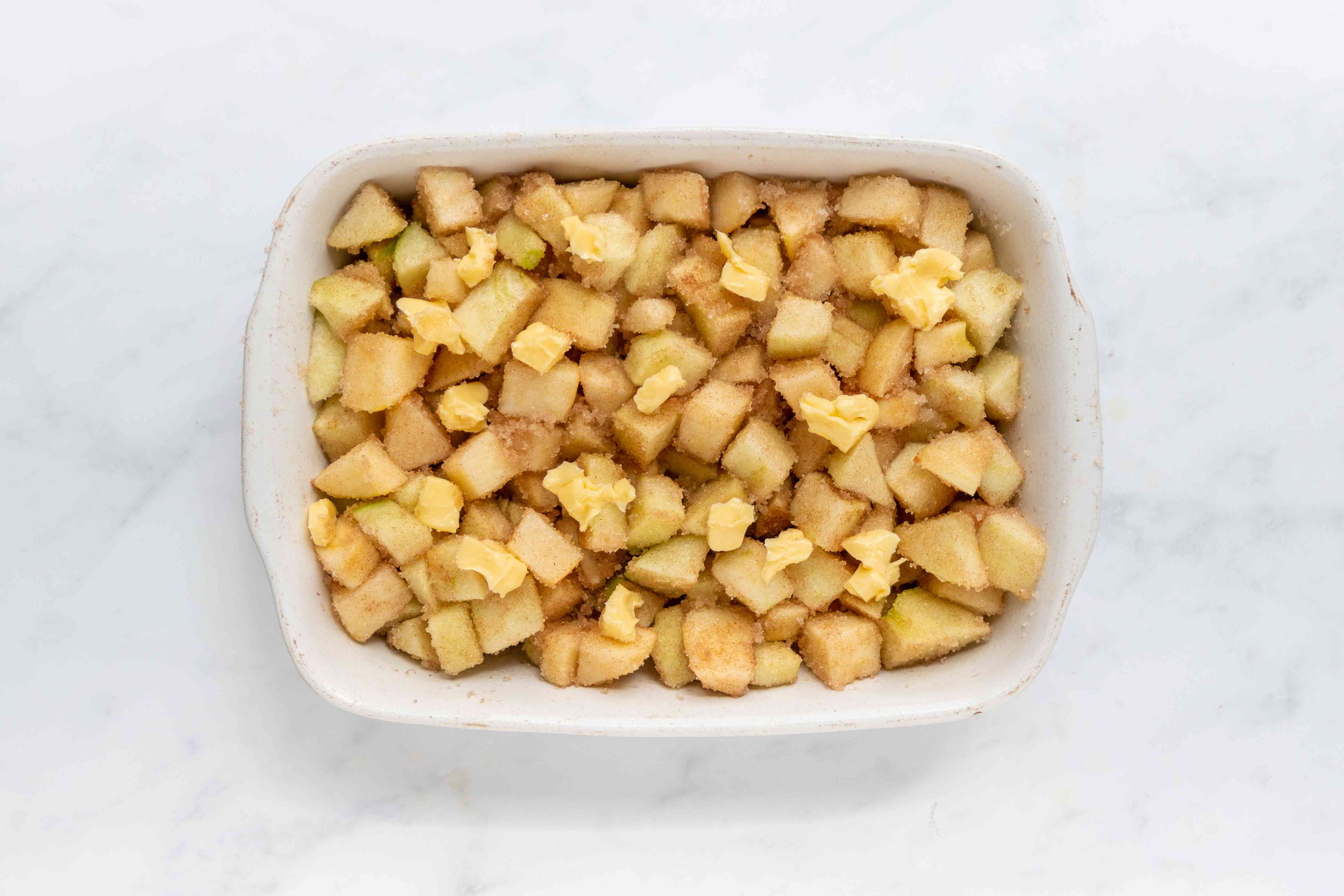chopped apples with sugar and the cinnamon in a baking dish, with butter on top