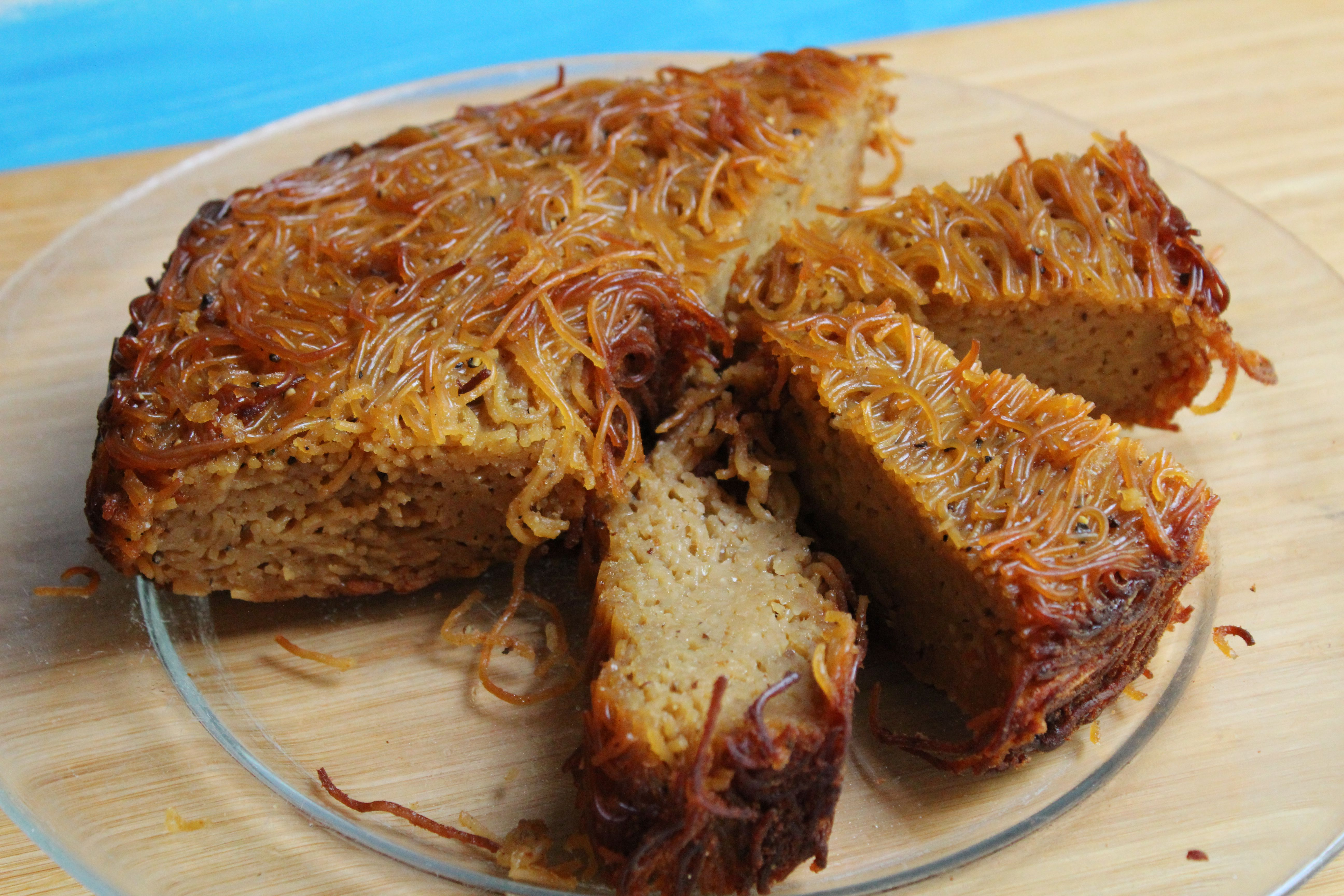 Jewish Yerushalmi kugel made with angel hair pasta cut into serving portions on a plate