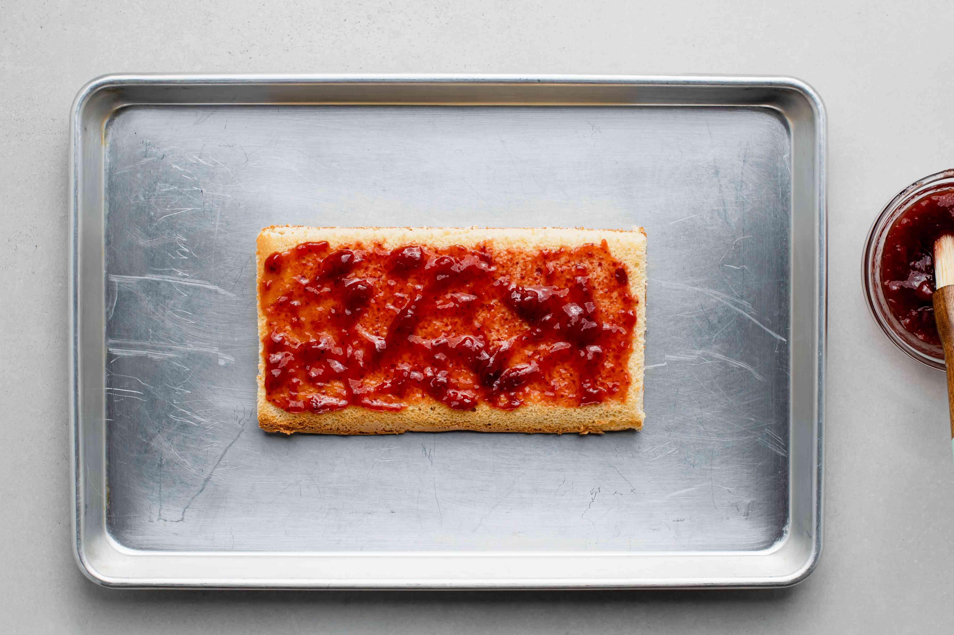 jam brushed over the cake on a baking sheet