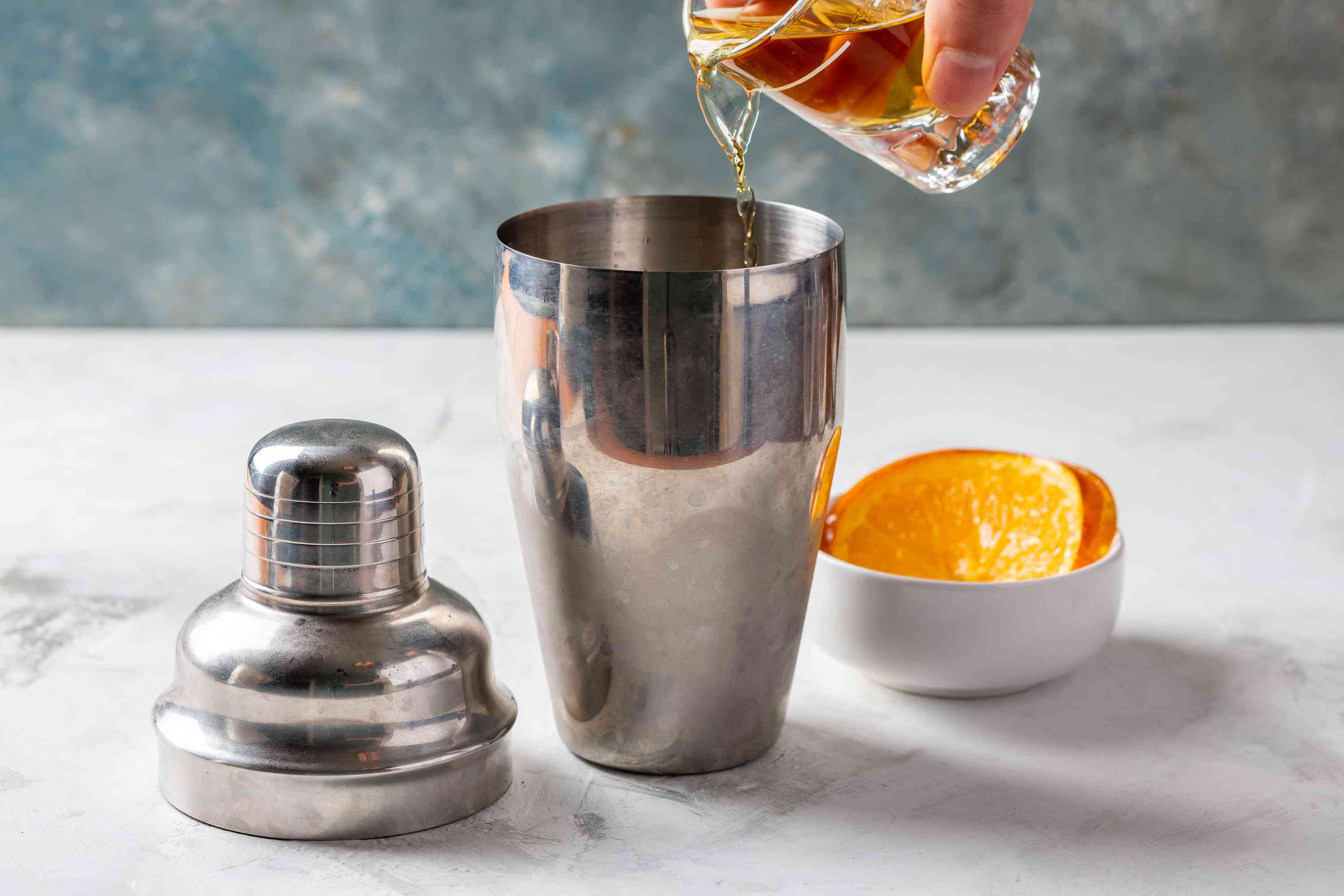 ice, bourbon, orange liqueur, sweet vermouth, and orange juice in a cocktail shaker