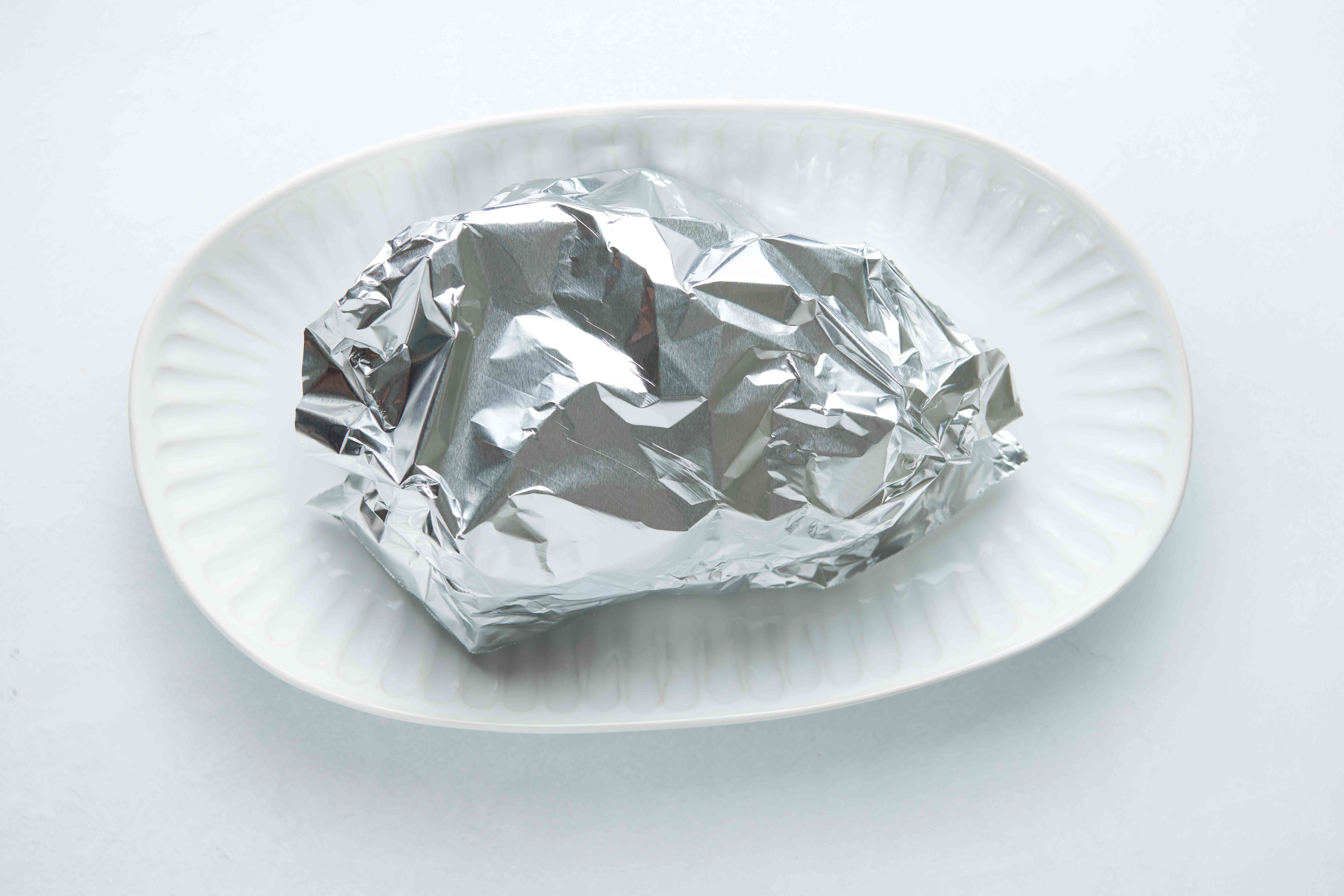 roast wrapped in a aluminum foil, on a platter