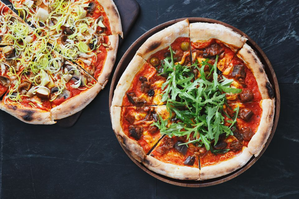 Pizza with eggplant, olive and arugula
