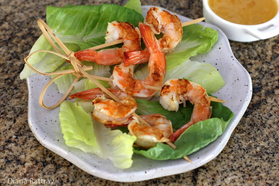 A plate of grilled shrimp with dipping sauce