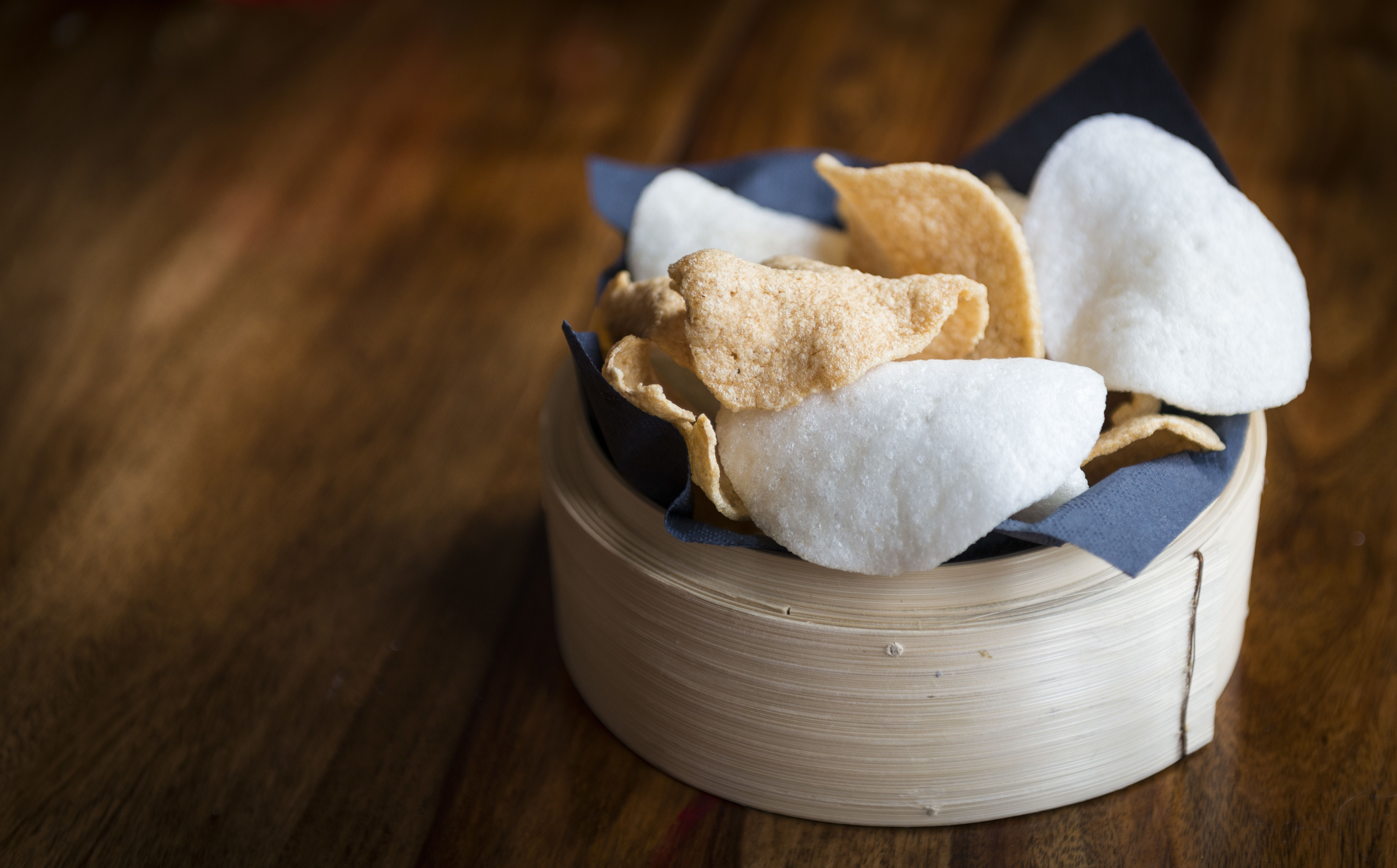 Prawn crackers in bowl on wooden table