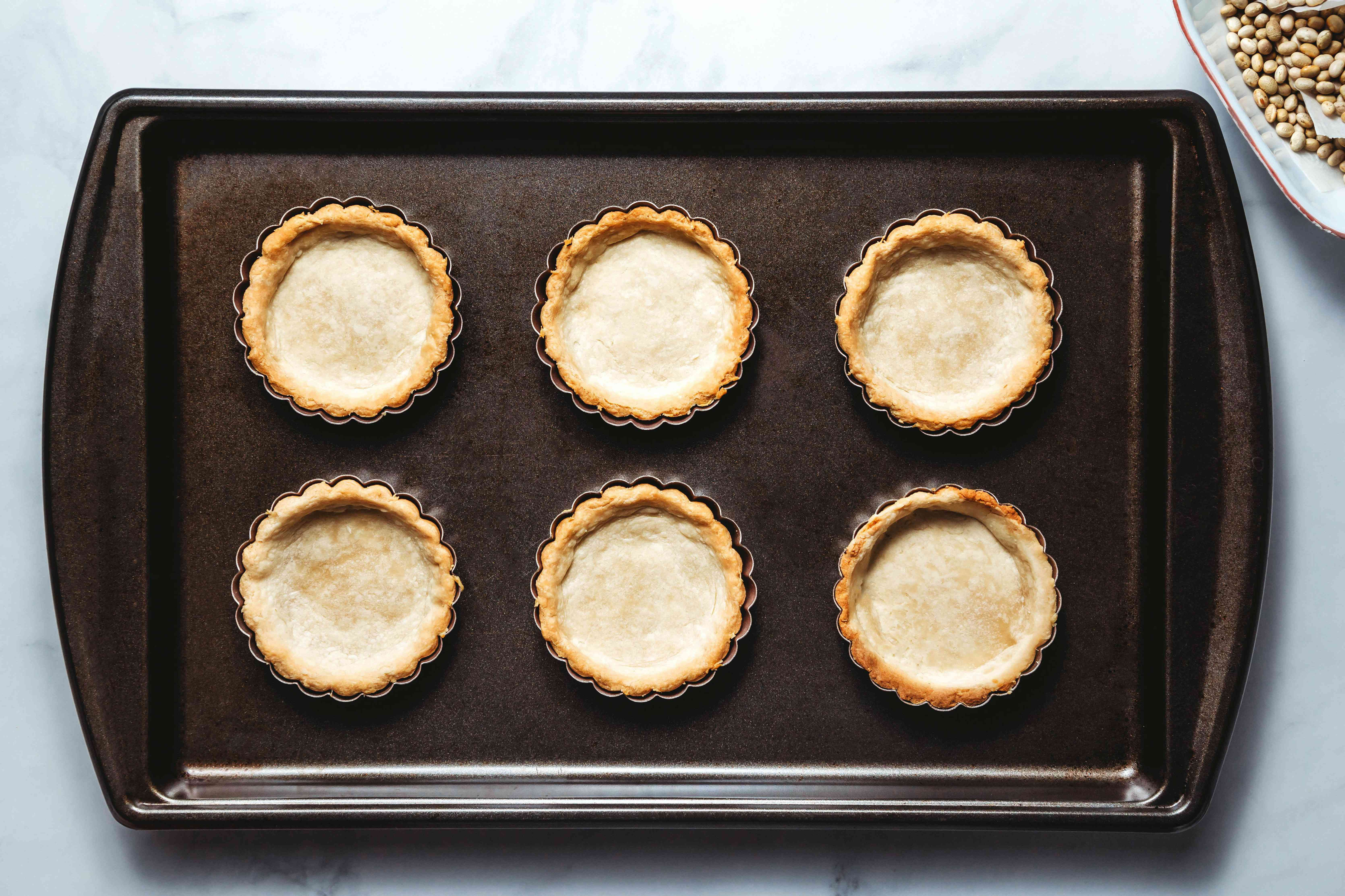 Remove the pie weights and the paper and let the shells cool all the way