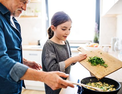 grandfather and granddaughter preparing food indoors in kitchen