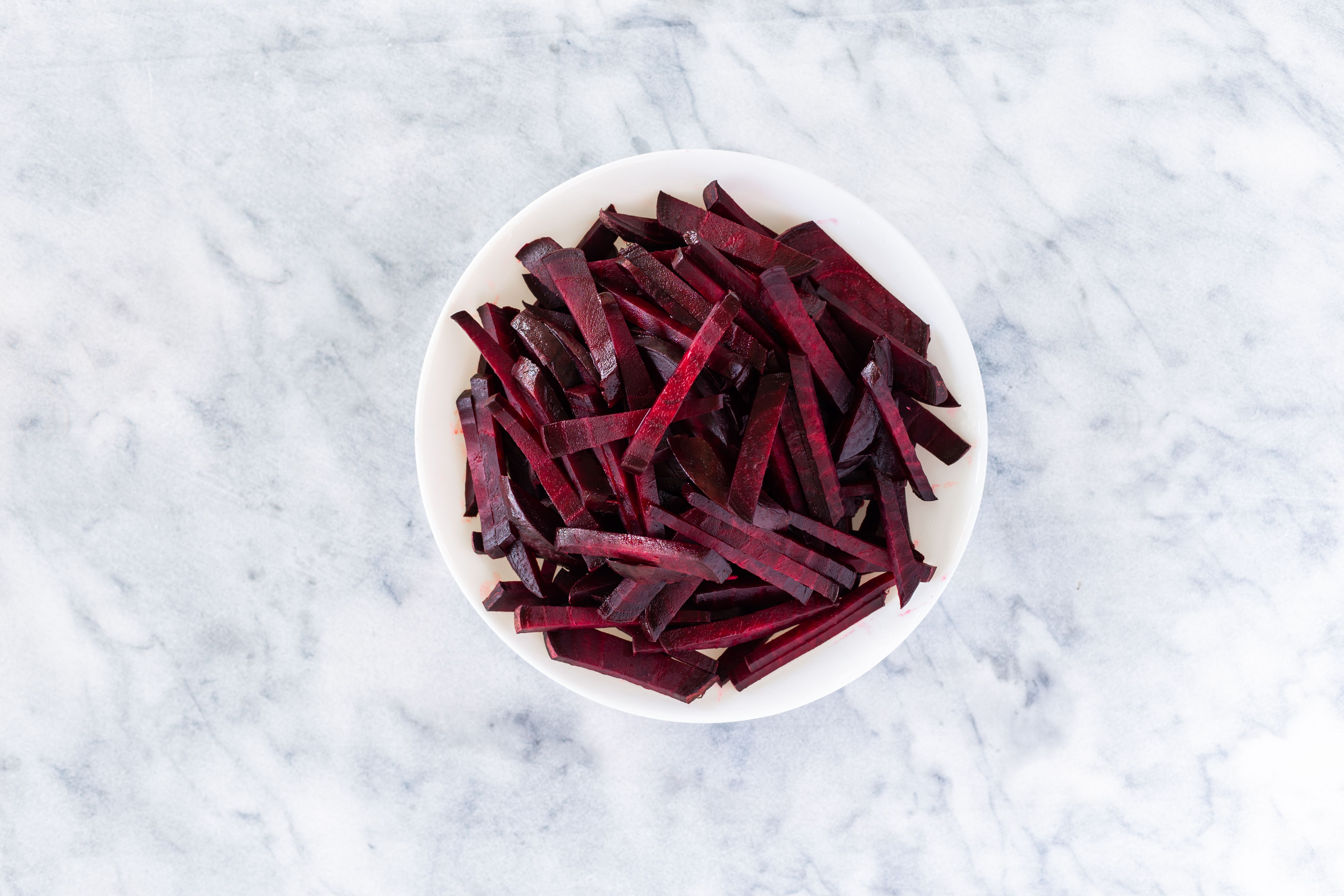 Julienned beets in a white bowl