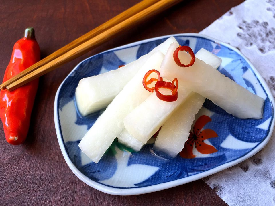 daikon radishes pickled on a blue china plate with wooden chopsticks on a wooden table and a chili chopstick rest