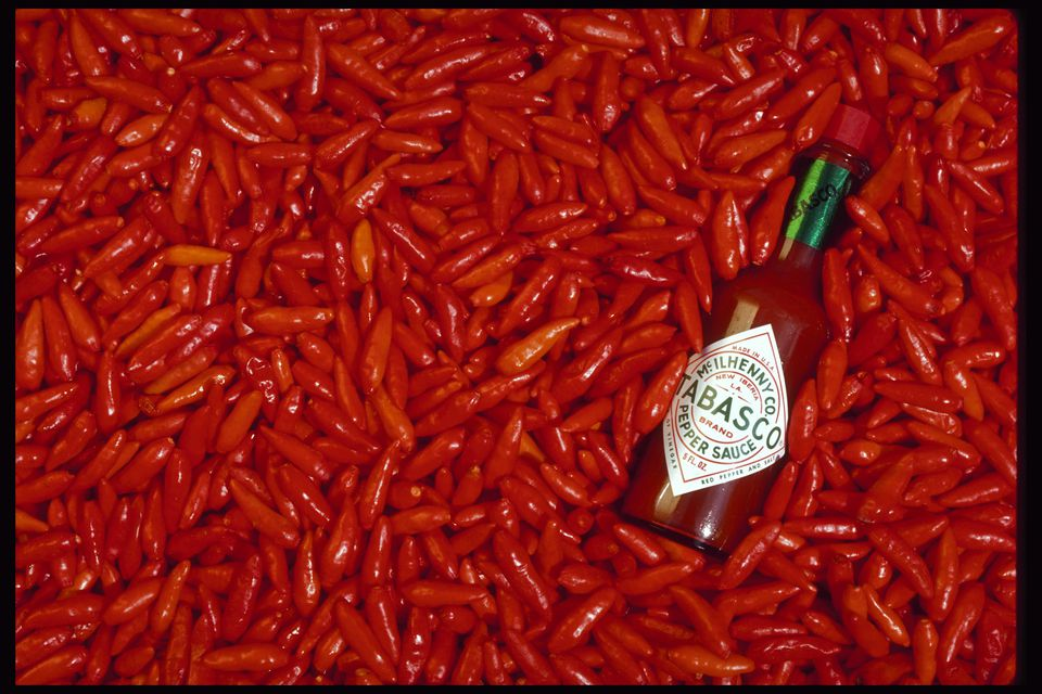 McIlhenny's Tabasco sauce amidst bright red tabasco peppers
