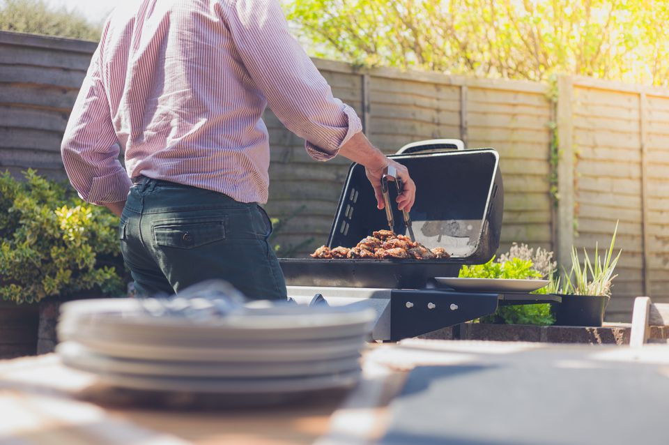 Man grilling chicken outdoors