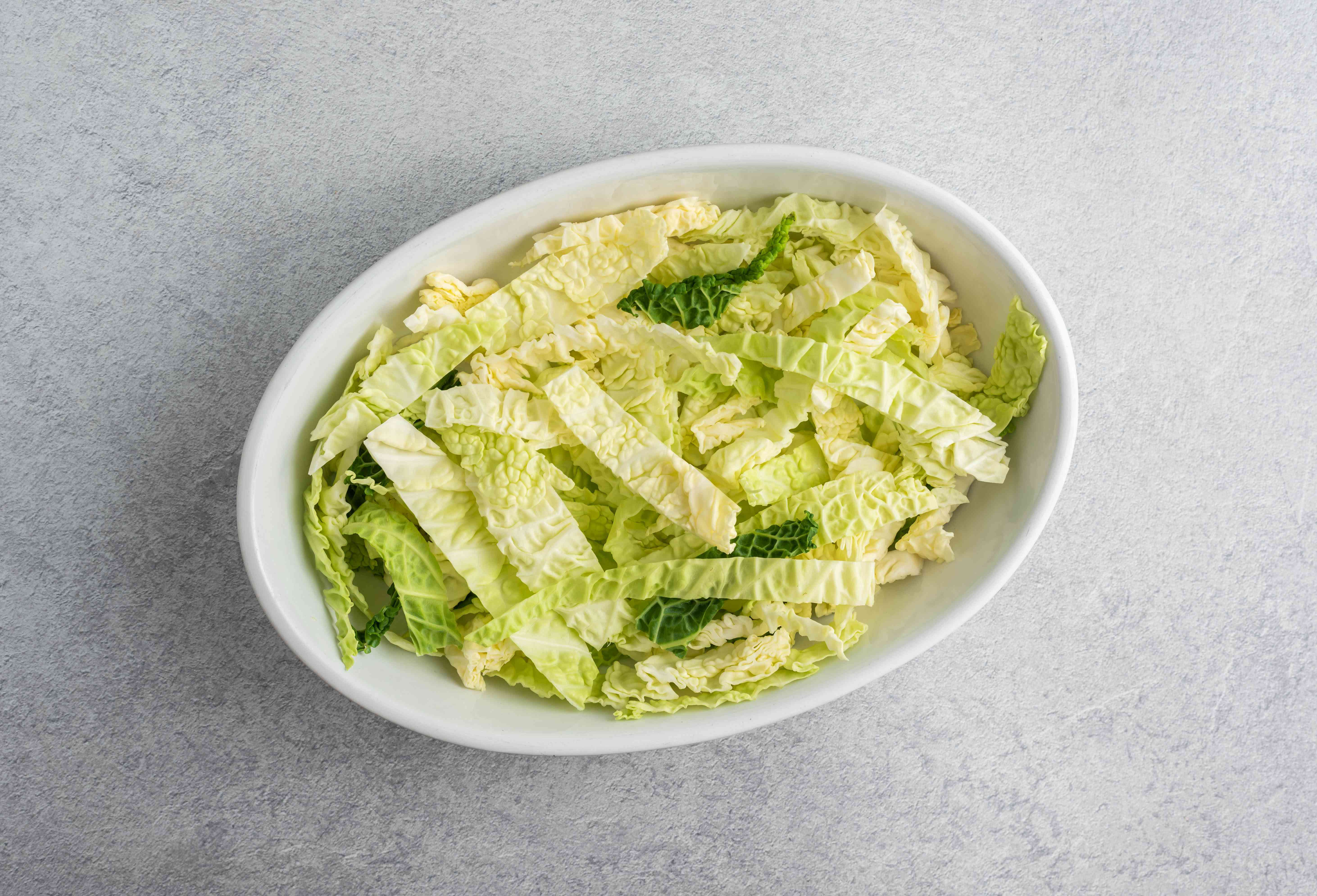 Thinly sliced cabbage in a white oval casserole dish