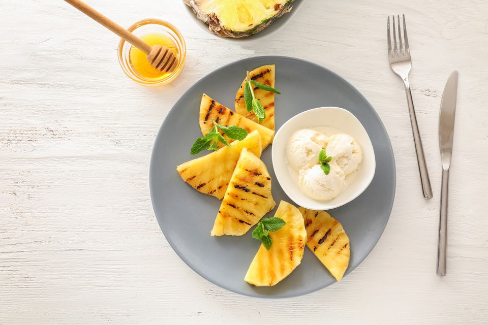 Plate with grilled pineapple slices and ice cream on wooden table