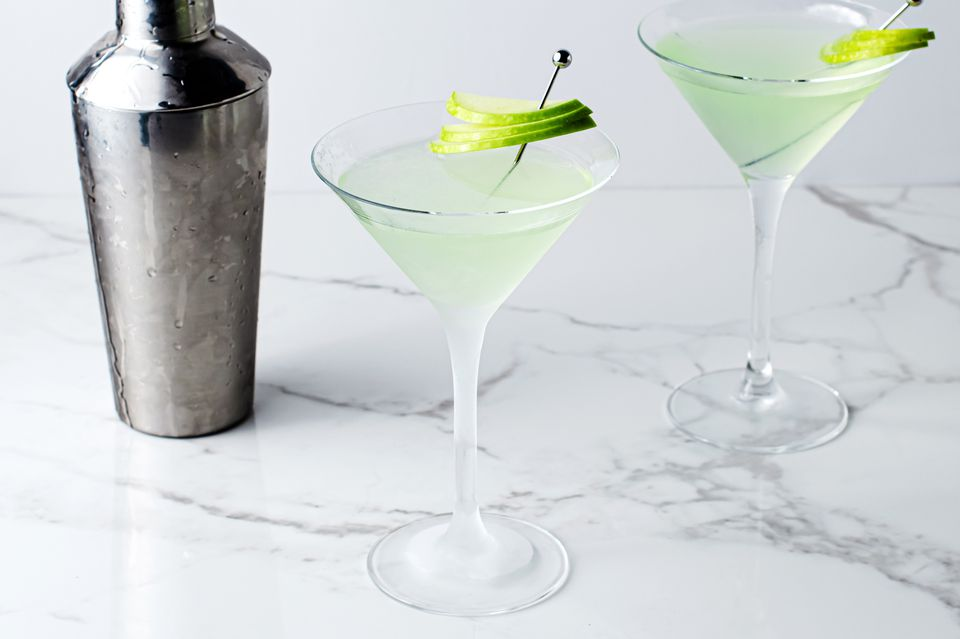green apple martini cocktails and a cocktail shaker on a marble table
