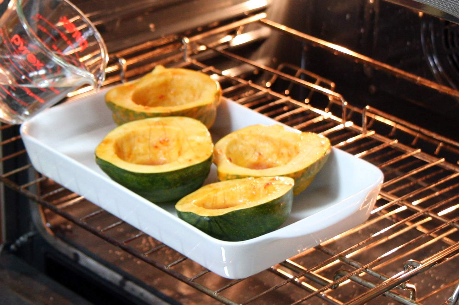 Adding water to the baking pan with the acorn squash