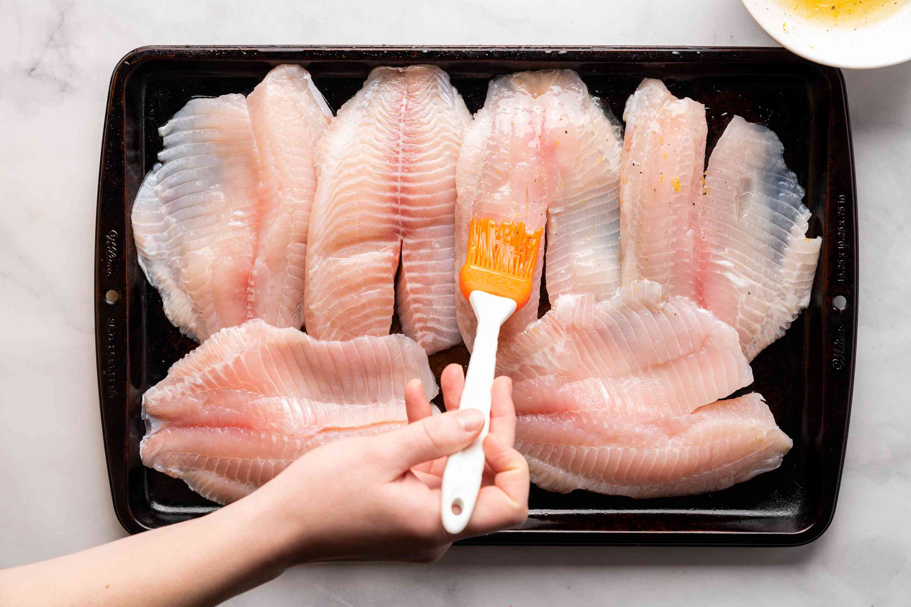 Brush the liquid mixture onto both sides of the tilapia fillets