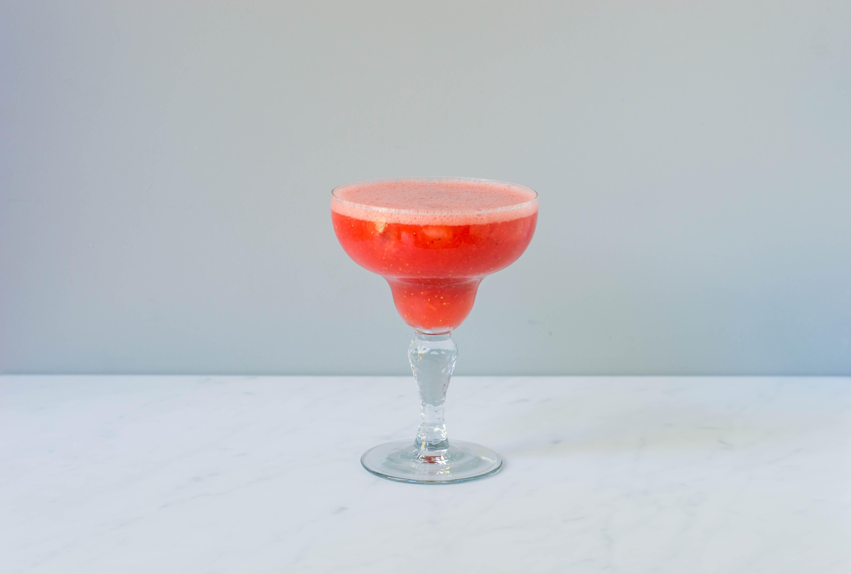 Pour strawberry margarita ingredients into margarita glass