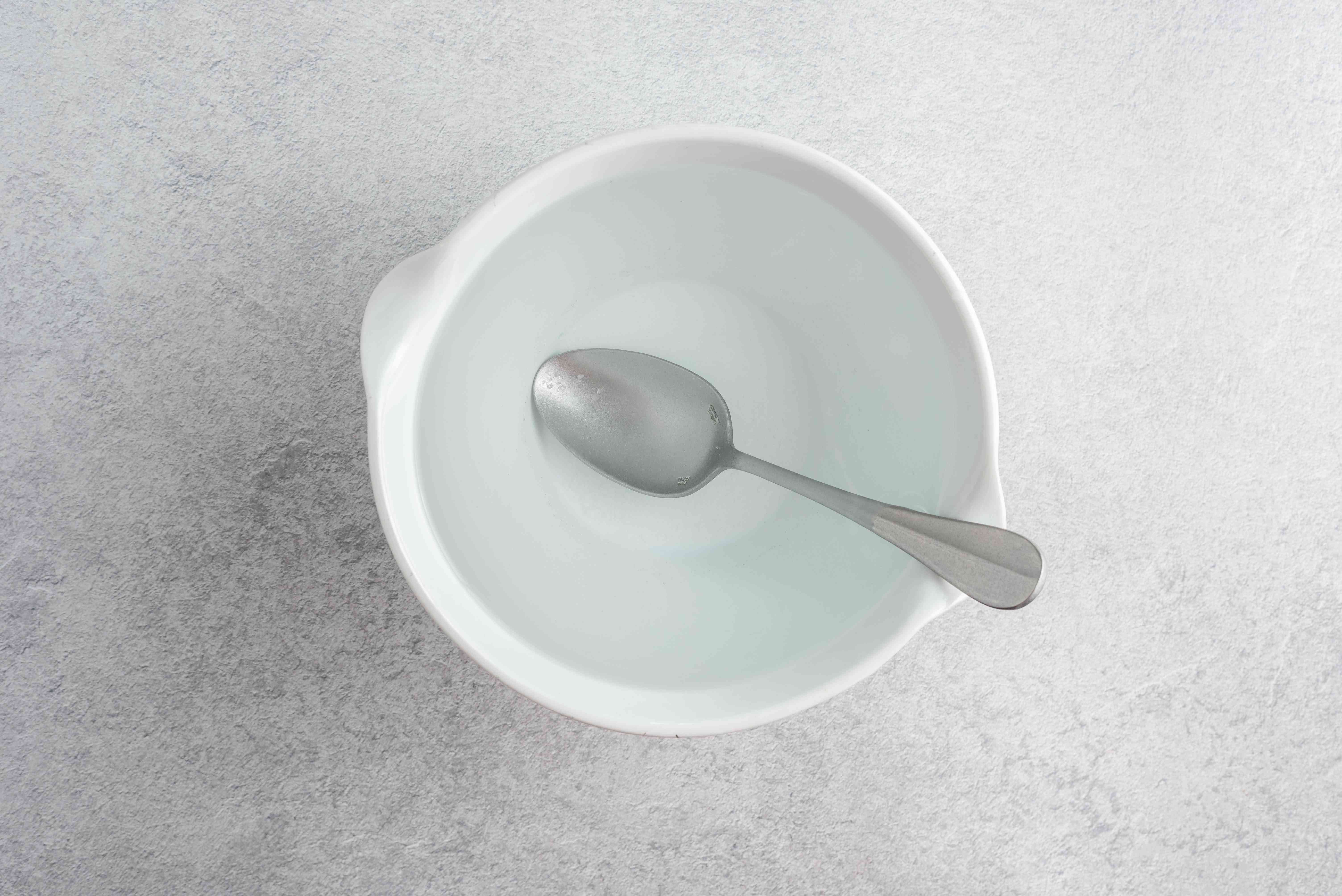 Water and salt mixed with a metal spoon in a white bowl