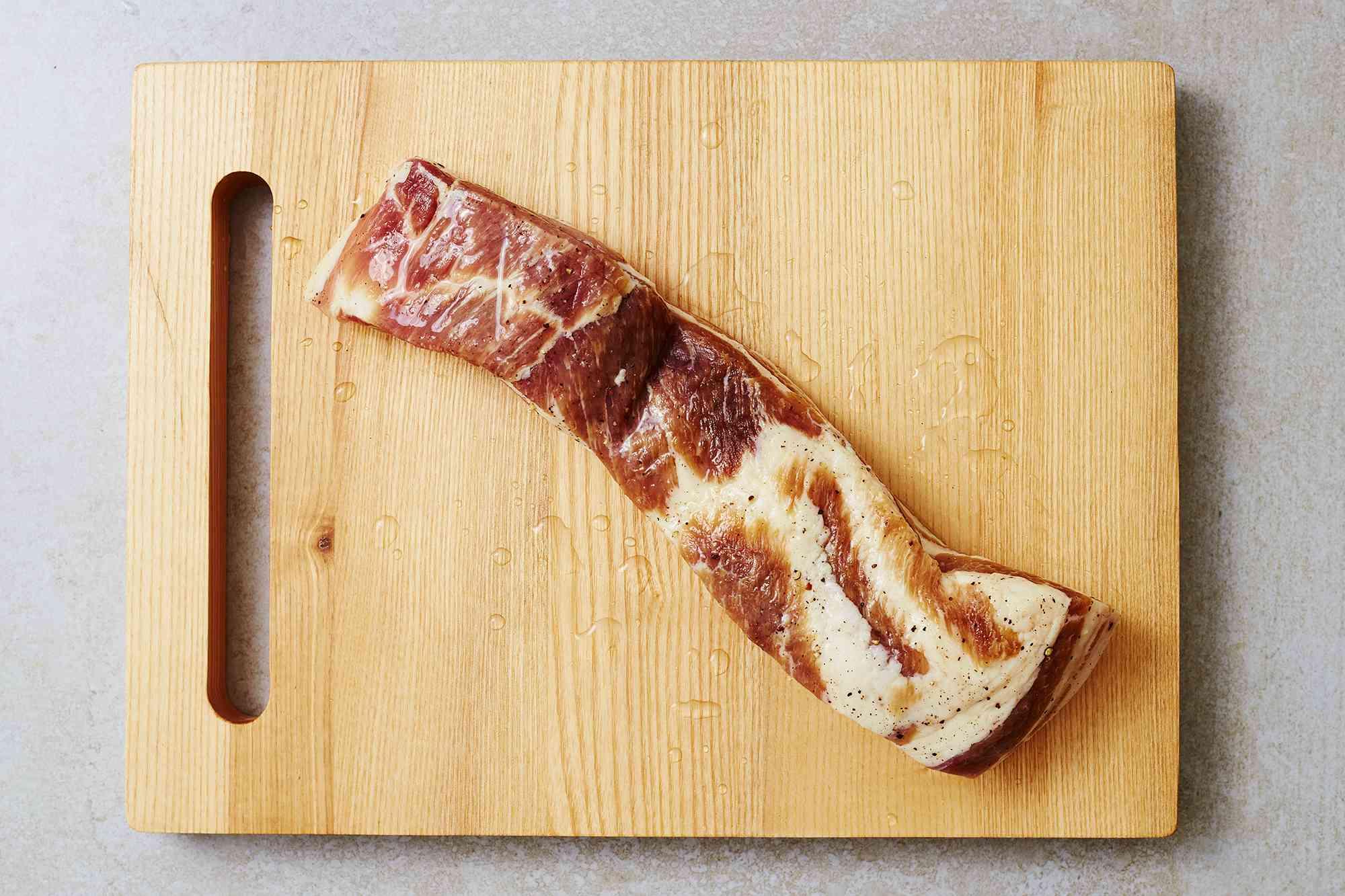 rinsed pork belly on a wood board