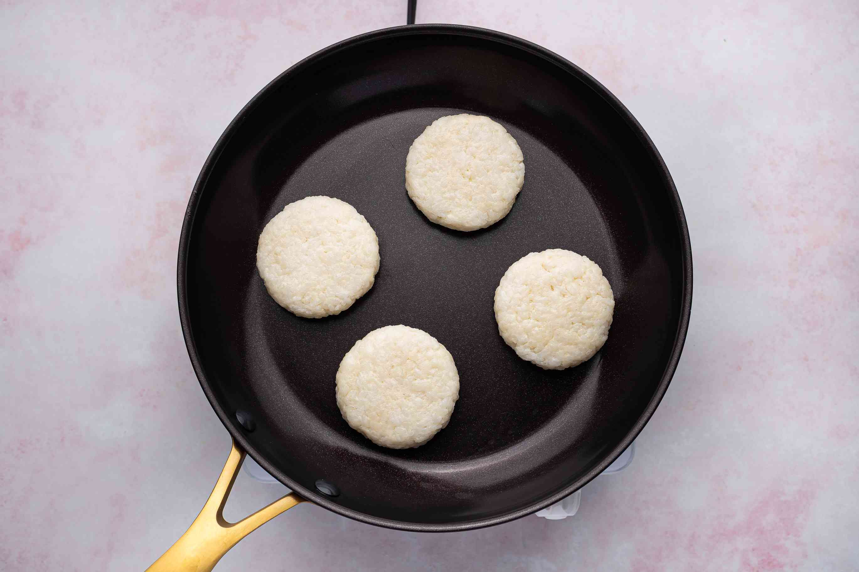 rice cakes frying in a skillet
