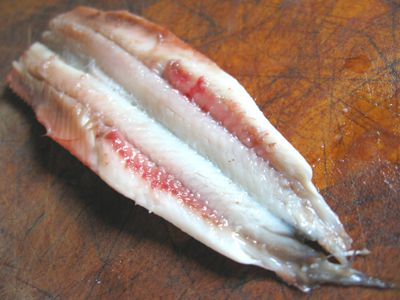 A filleted, split anchovy