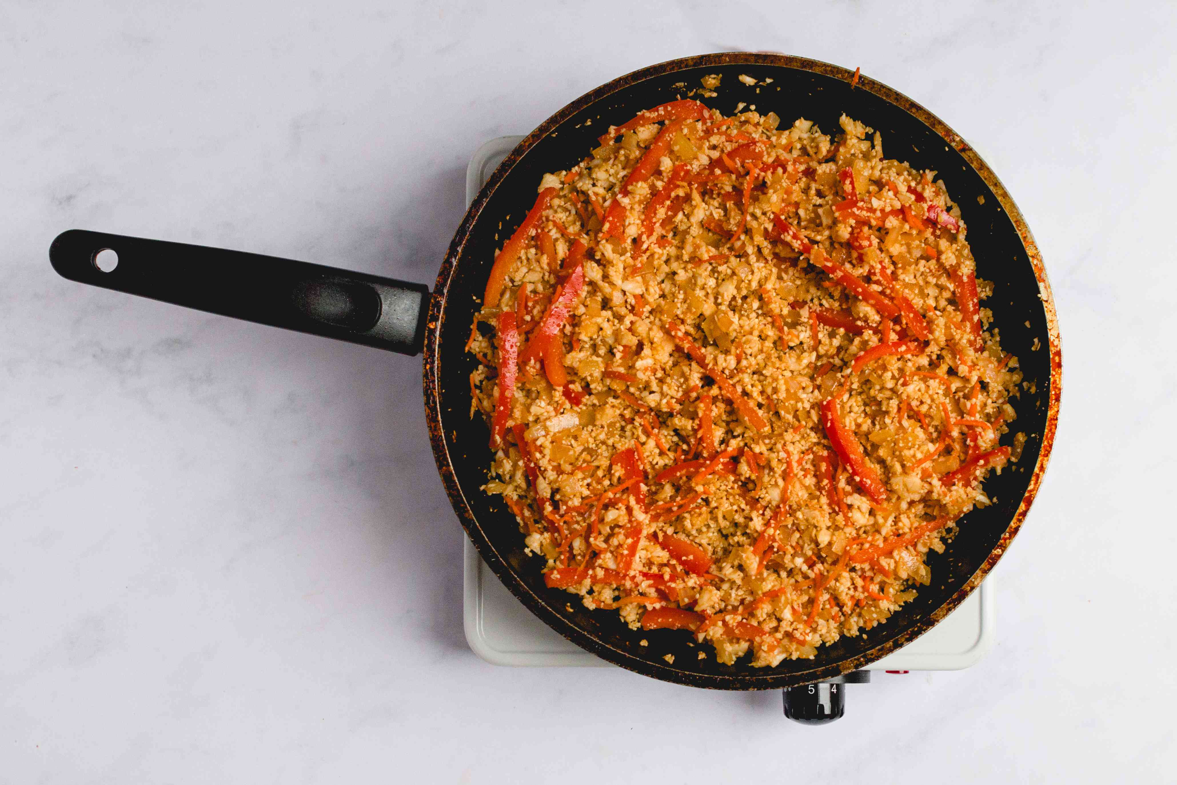 cauliflower fried rice cooking in a pan