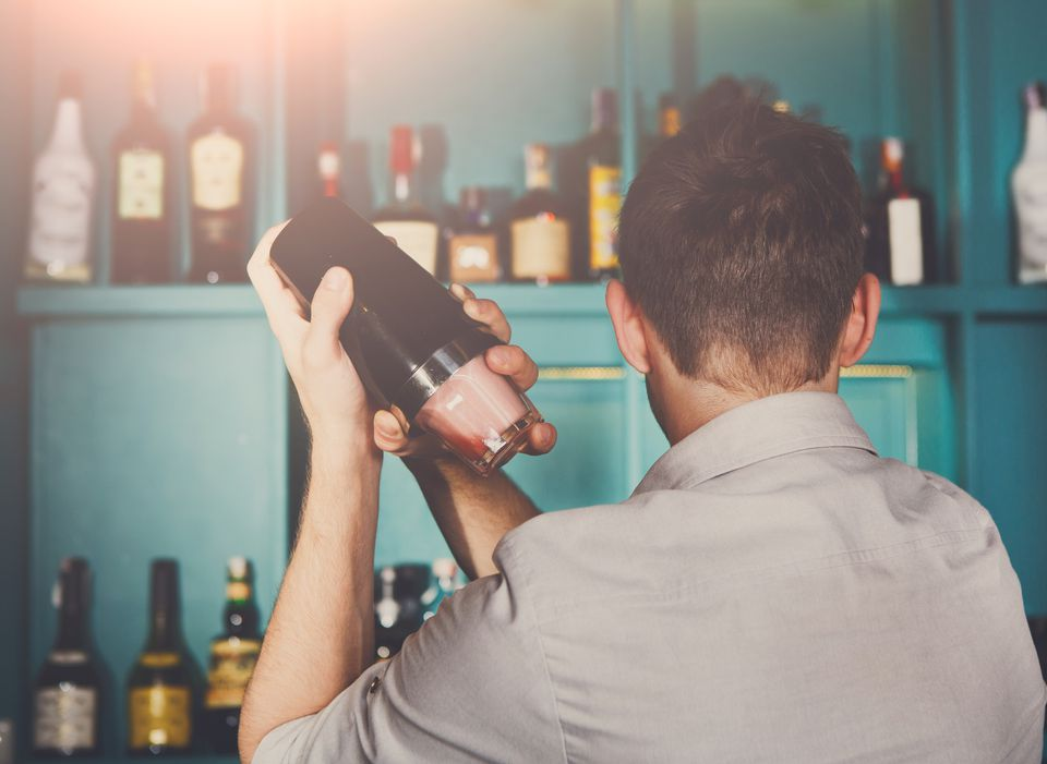 Young male bartender shaking a cocktail