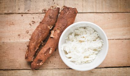 Fresh cassava (yuca) roots look brown and woody, while freshly grated raw look pure white